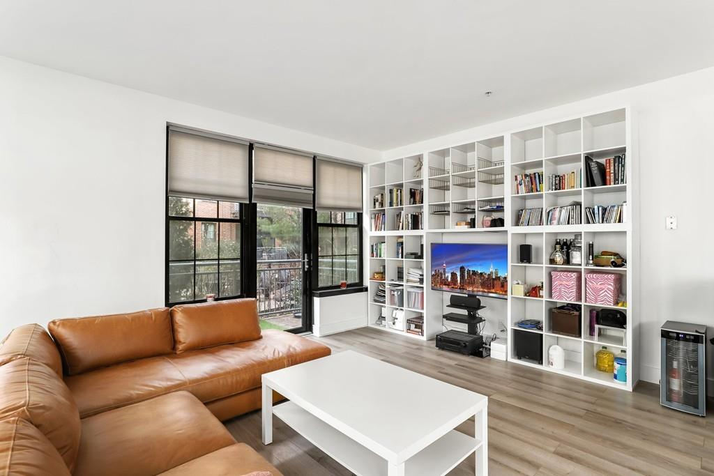The spacious corner of a spacious living room with a sectional couch facing a set of shelves.