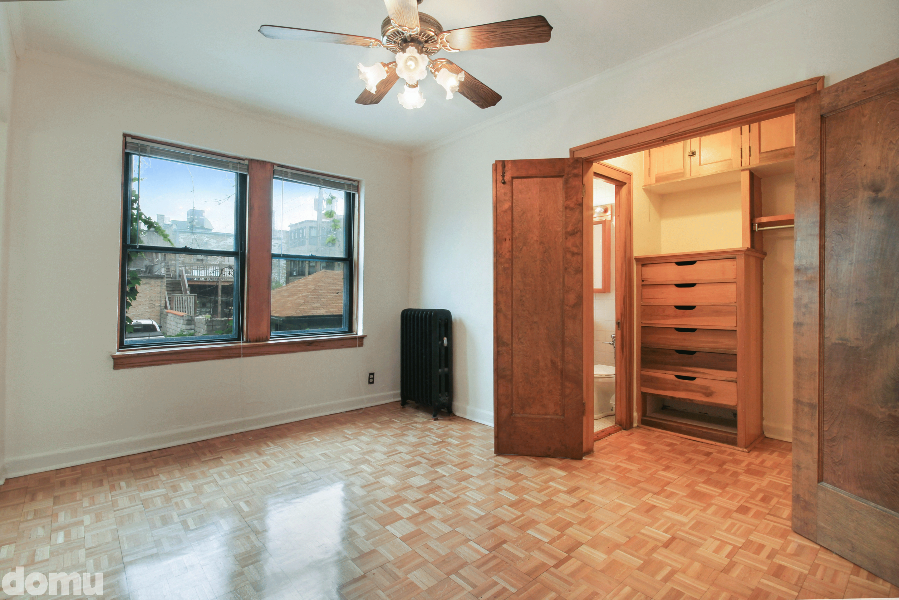 An image of a bedroom with parquet floor and large window. It has a closet with built in shelving and an en suite bathroom.