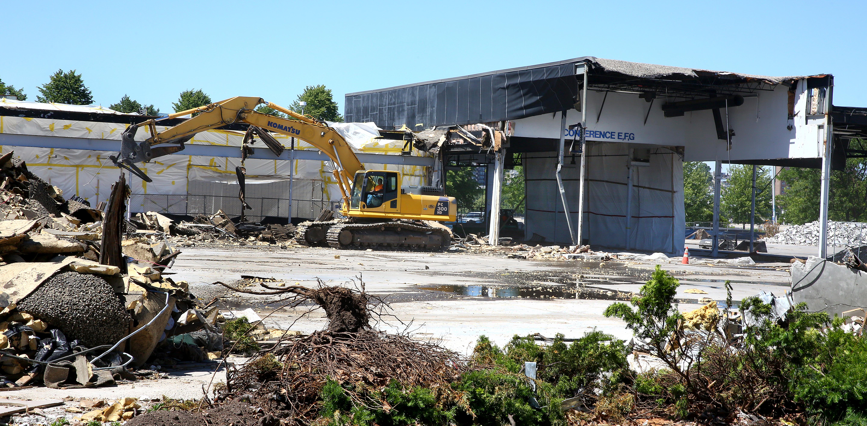Construction equipment demolishing an old mall site.
