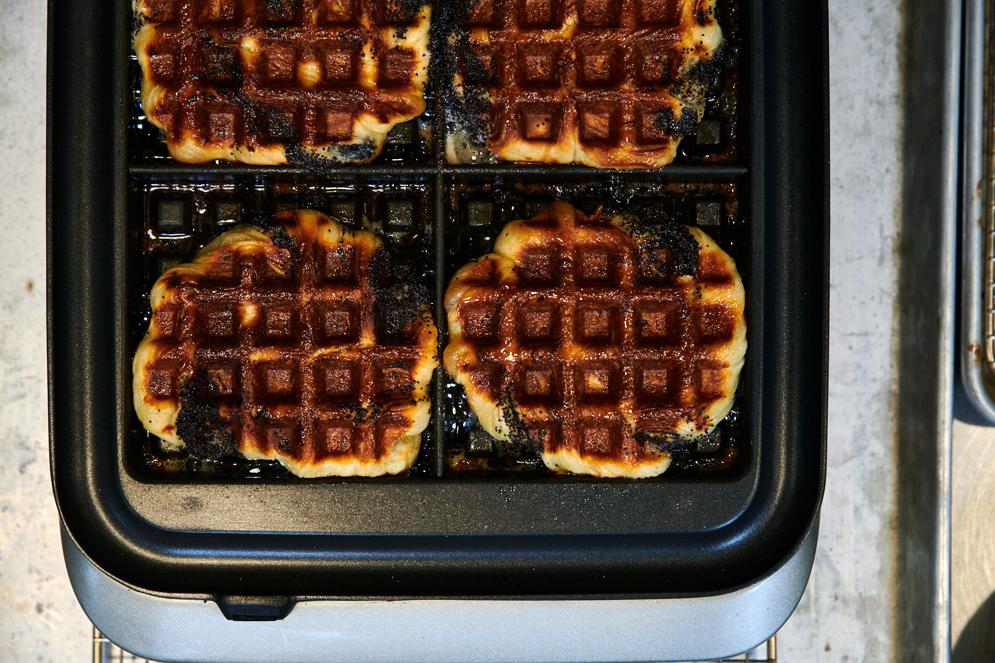 Four babka waffles sit in the waffle press at Ava Gene's. The sugar on the outside of them has created a caramelized brown on them, with patches of black from the poppyseeds
