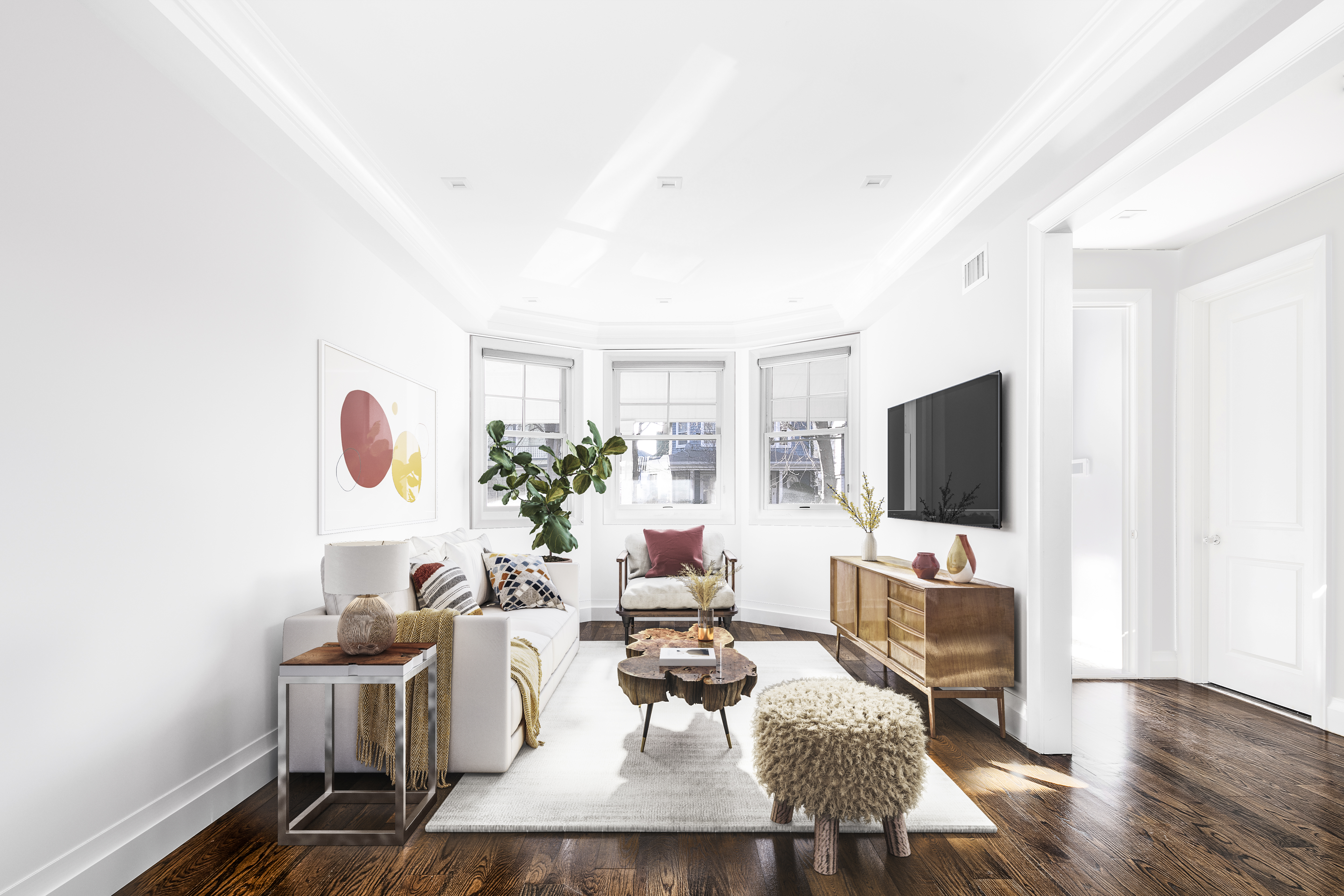 A room with white walls, a TV mounted on one wall, large windows, and a white couch.