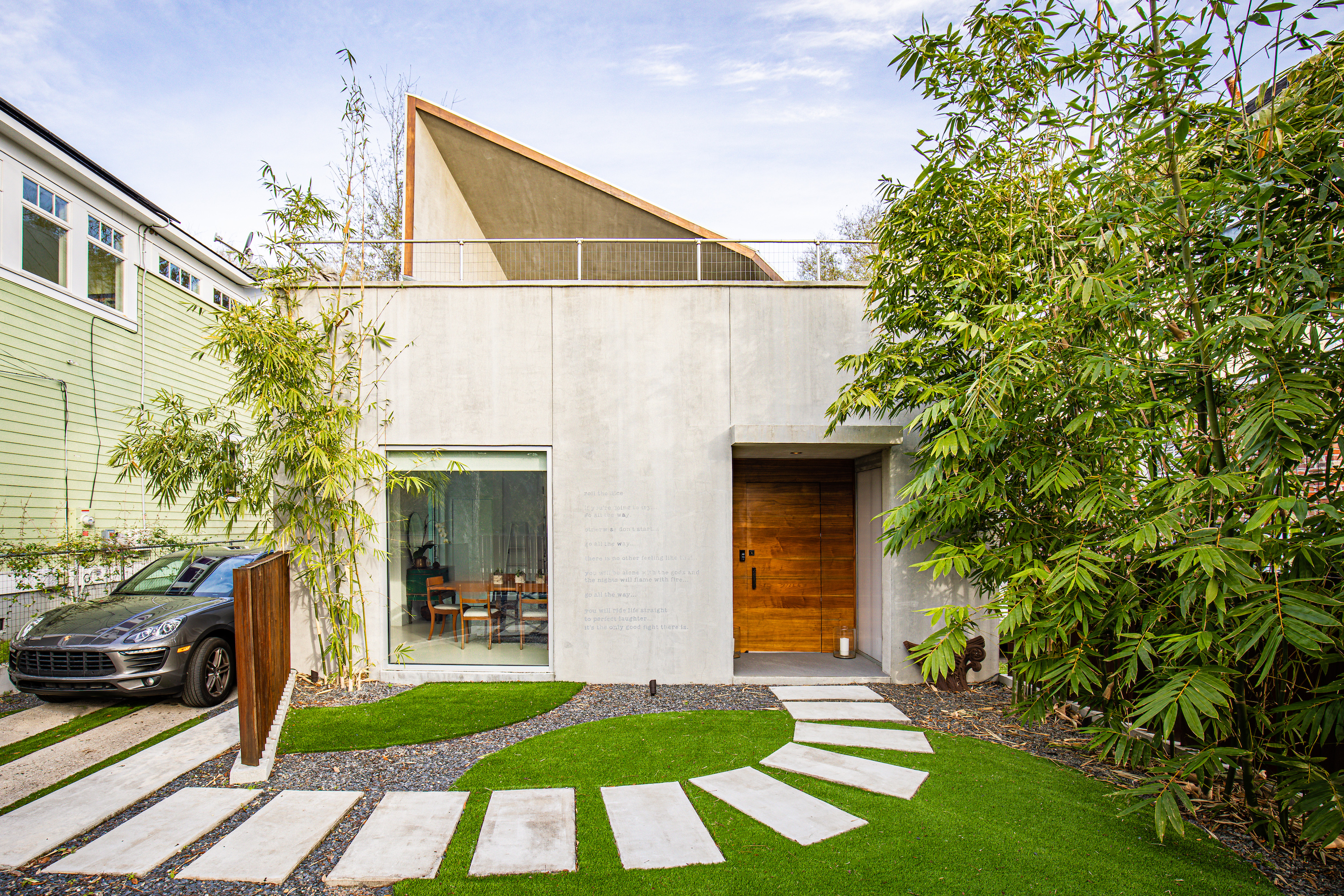 A boxy concrete home features an angled roof and a green yard with cement path.