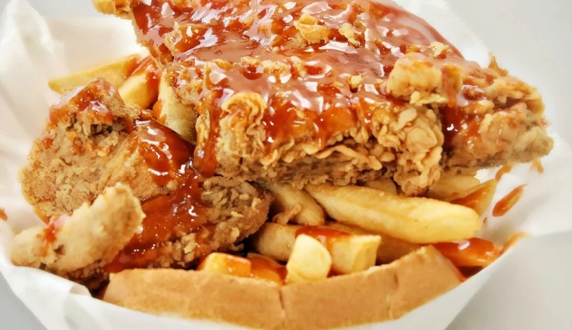 A plate of fried chicken and french fries smothered in sauce.