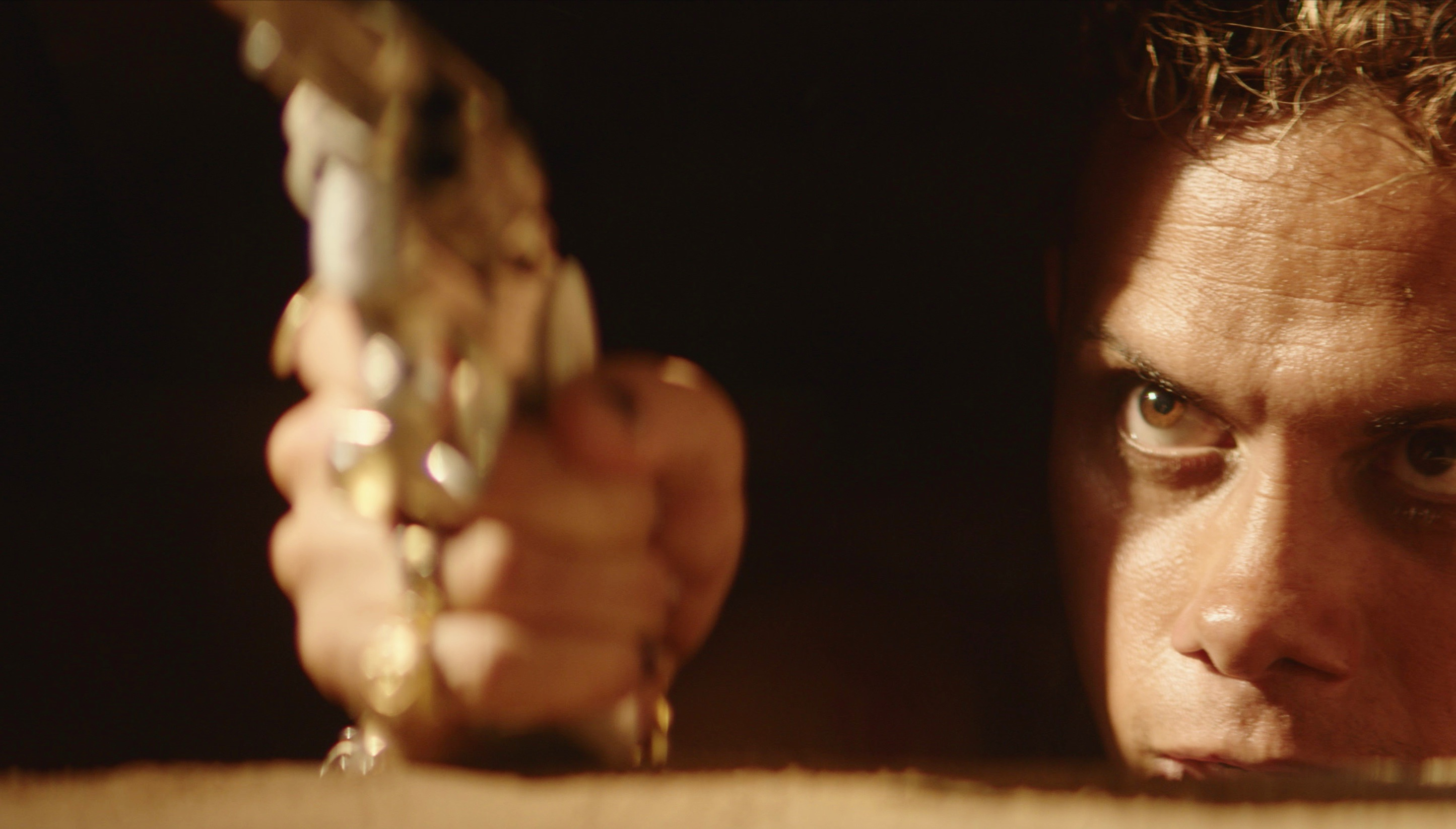 An extreme closeup of a glowering brown-eyed man peering up from a pit, pointing a shining handgun up at something above camera level.