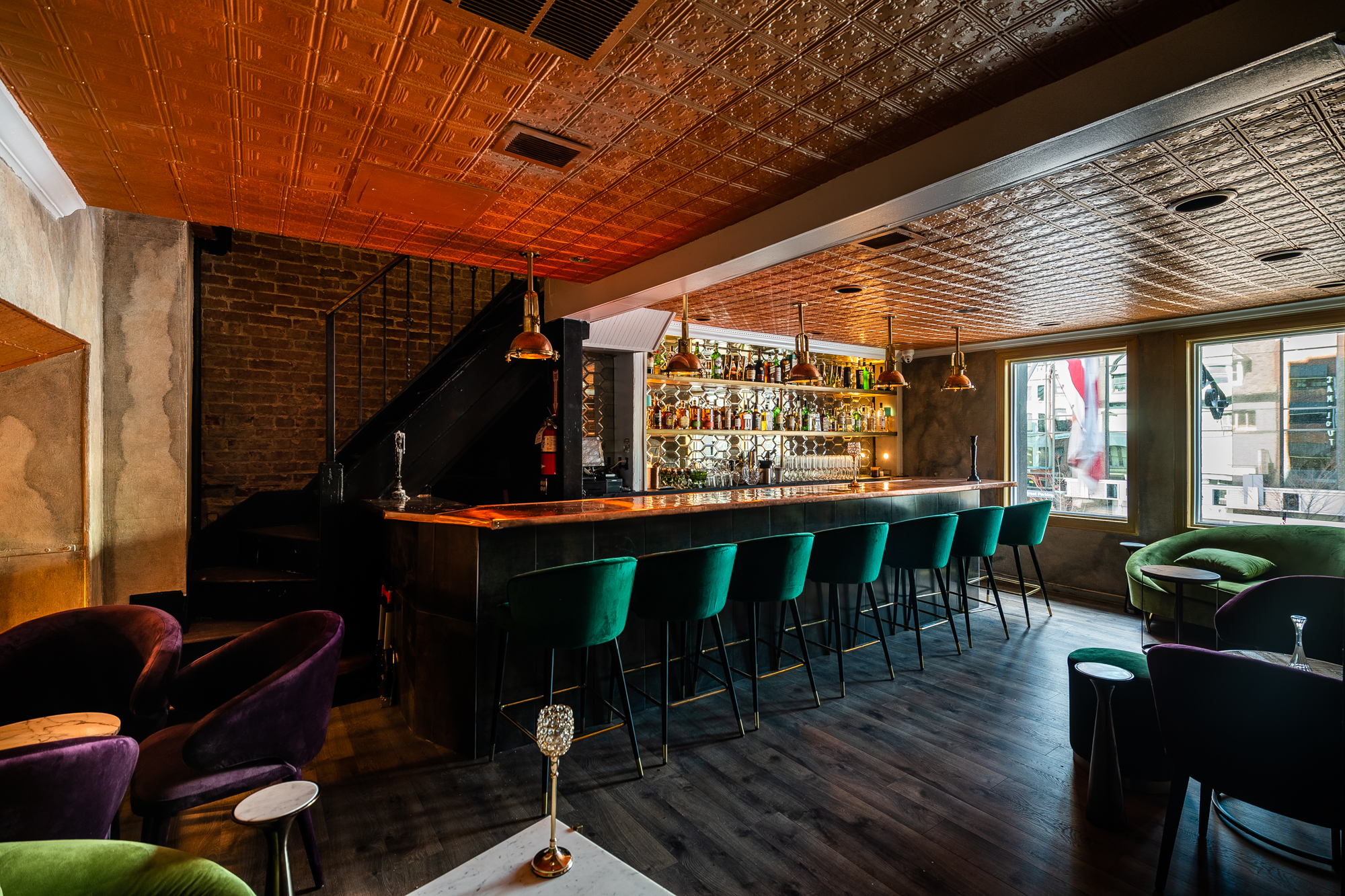 """Jewel-toned velvet seating and a geometric mirror-lined bar backsplash occupy the upstairs """"VIP"""" section."""
