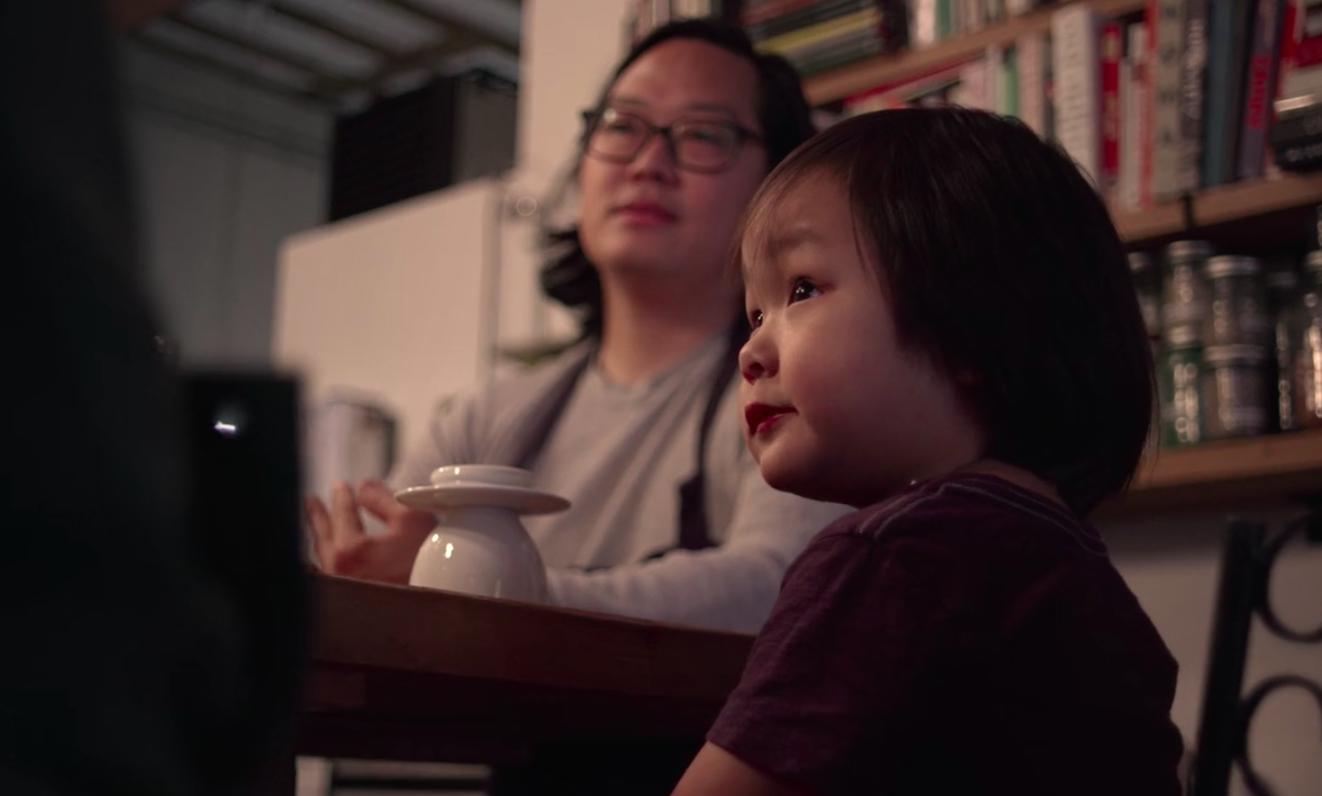 Peter Cho, with long hair and glasses, looks at an out-of-frame David Chang. His five-year-old son, Elliot, sits at the chef's counter of Han Oak, staring at Chang.