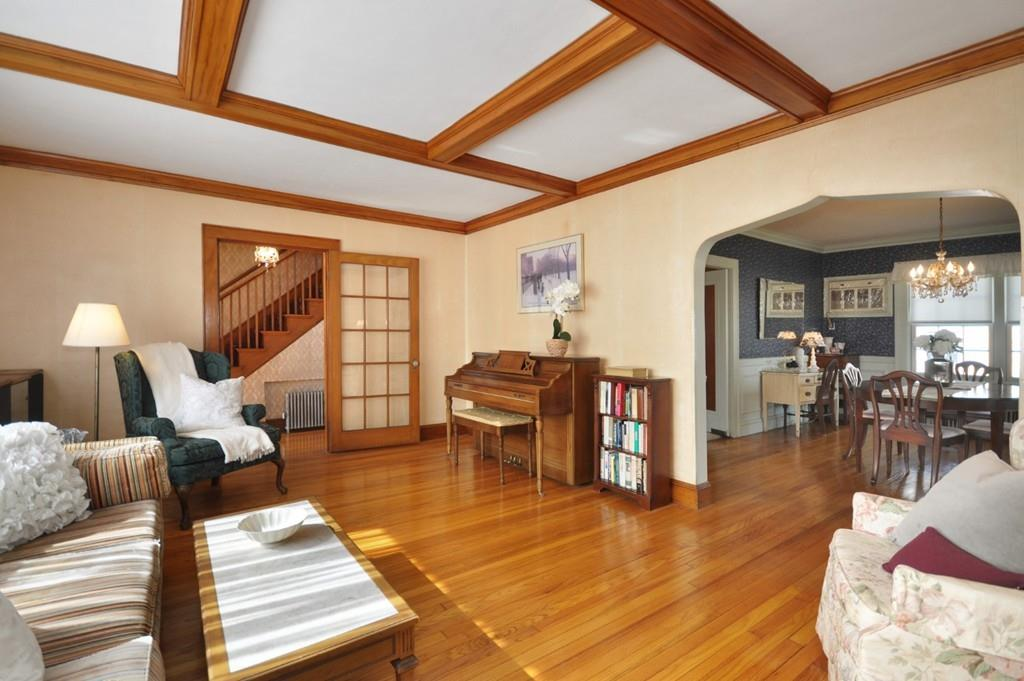 A living room with furniture, including a piano, next to an entry hall and leading to a dining room.
