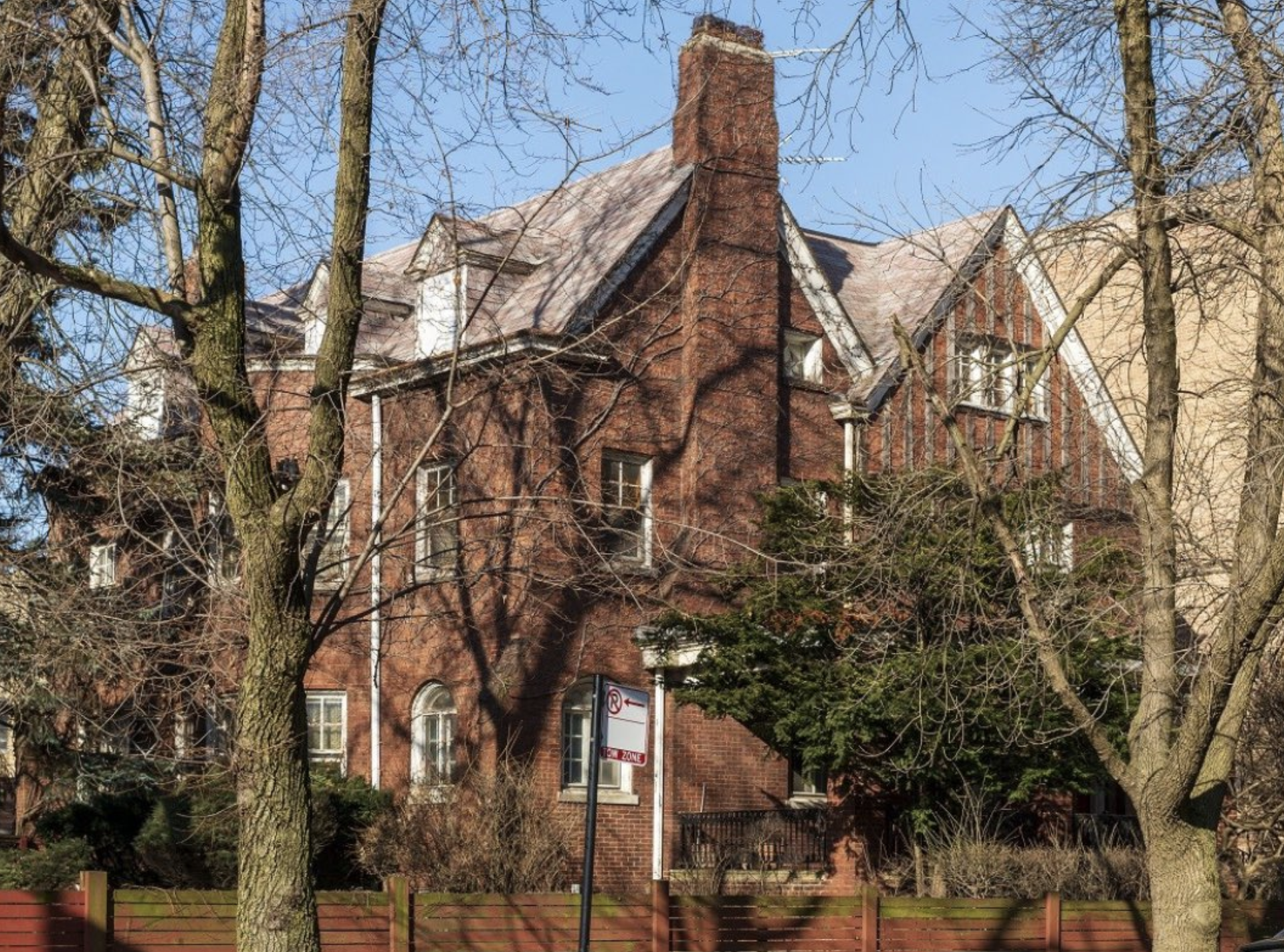 A view of a three-story brick building with steep gables and a chimney. There are trees and landscaping around the building