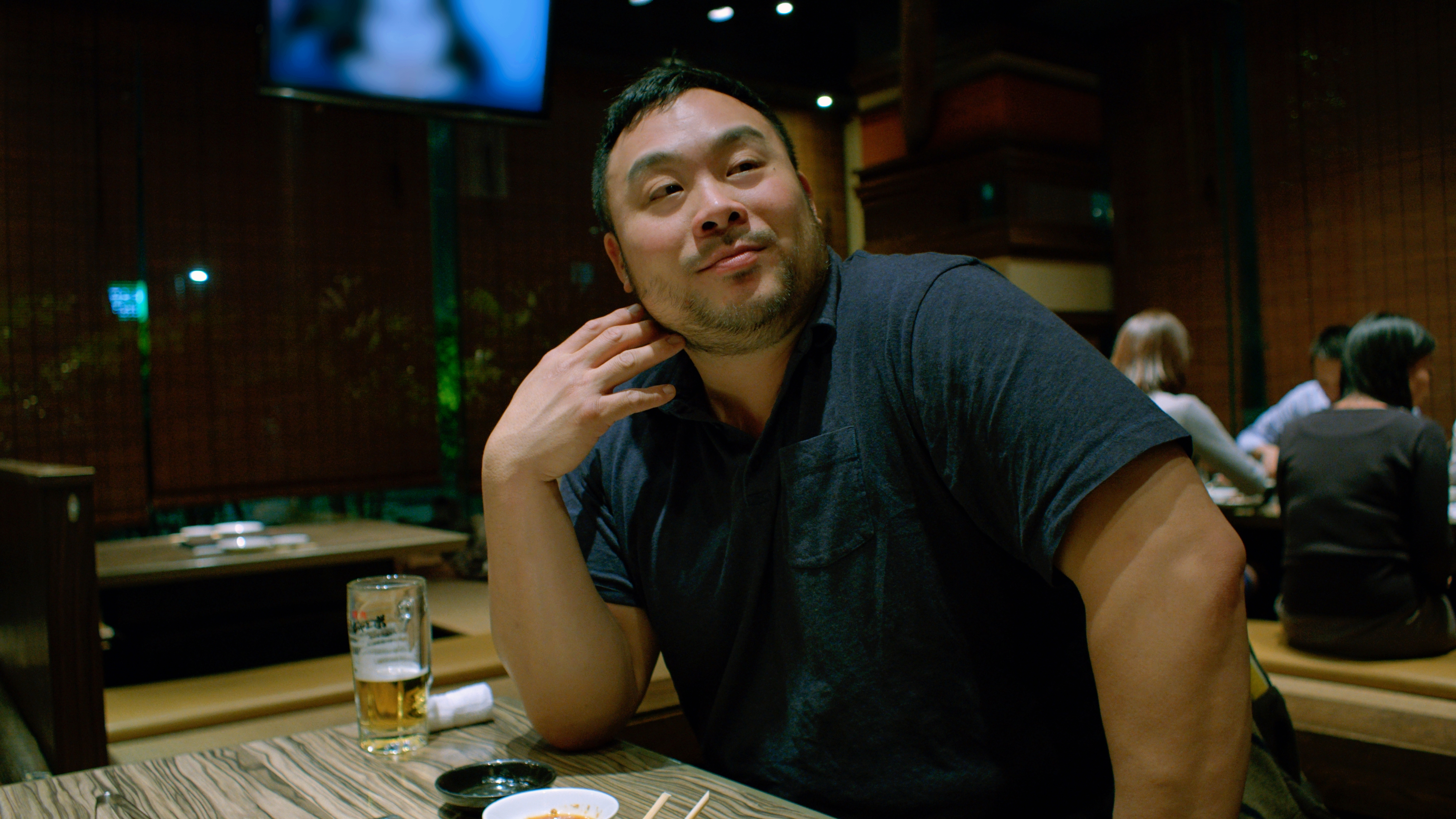 David Chang seated at a table in a Japanese restaurant.
