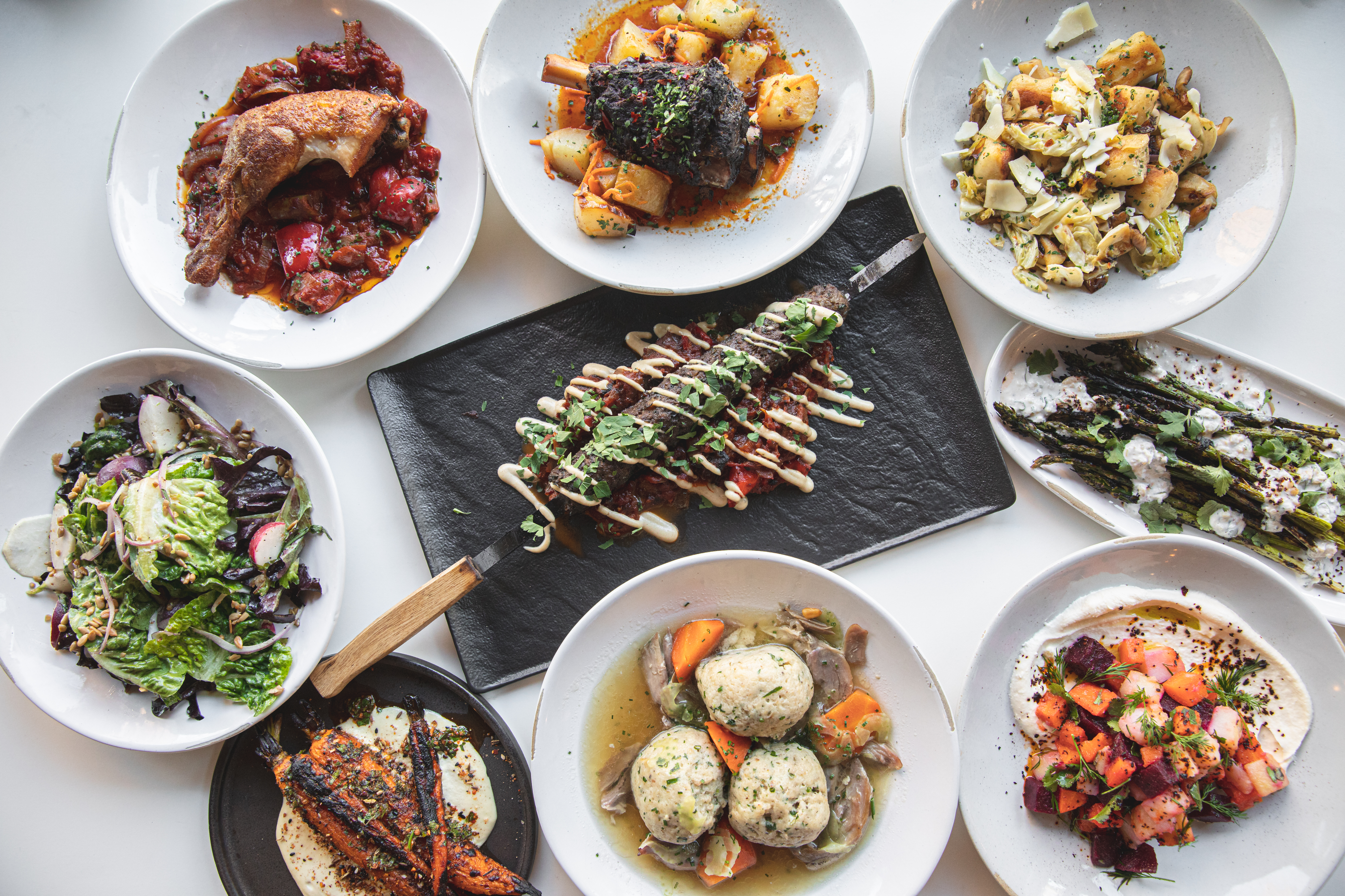 A white table is covered in plates from Y'alla, including a Bulgarian kebab at its center, a plate of matzo balls, roasted spring carrots with salsa verde, chicken confit with tomatoes, and more