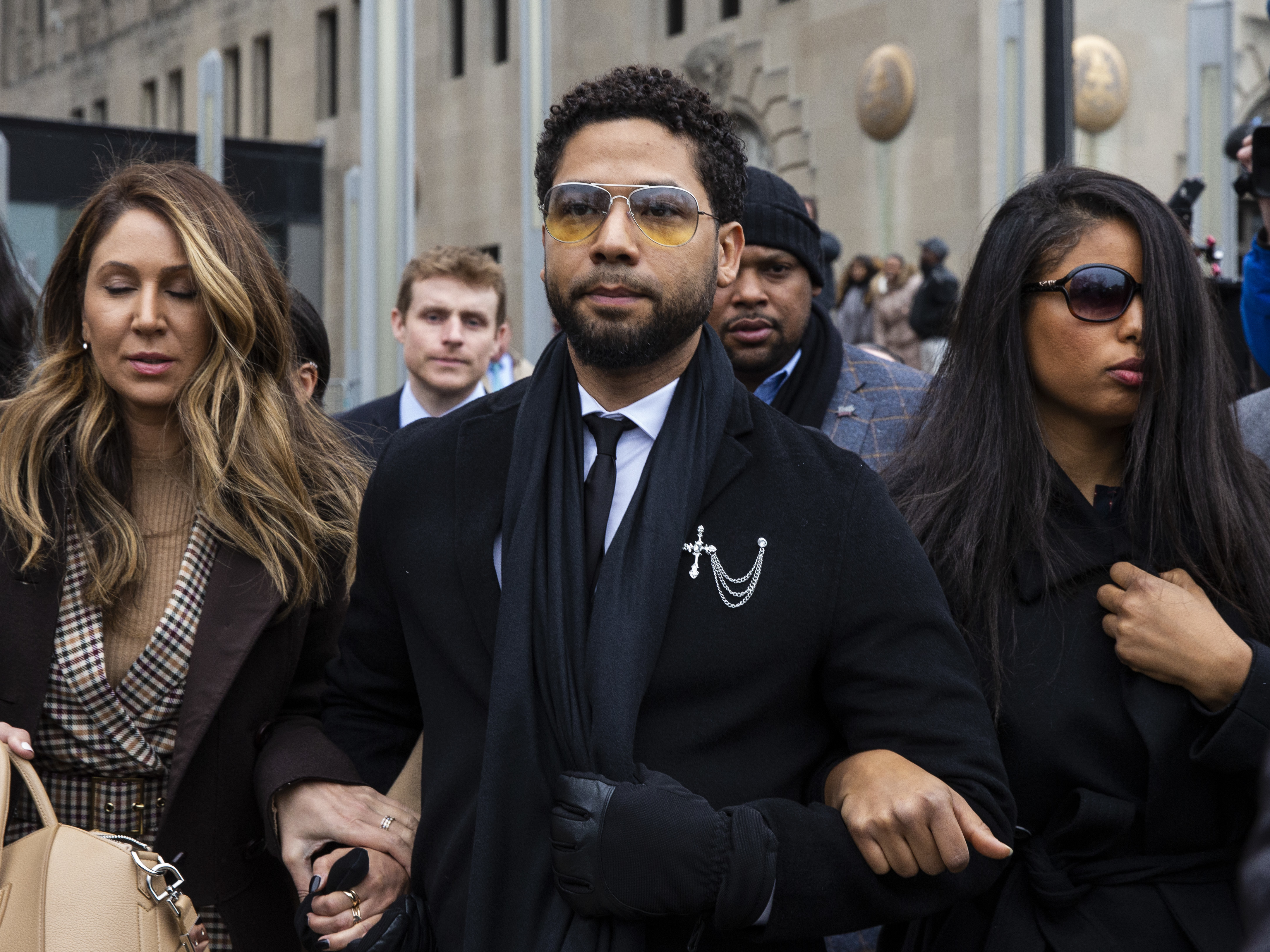 """Flanked by attorneys and supporters, former """"Empire"""" actor Jussie Smollett walks out of the Leighton Criminal Courthouse after pleading not guilty to a new, six-count indictment charging him with falsely reporting he was the victim of a hate-crime attack near his Streeterville apartment in January 2019, Monday morning, Feb. 24, 2020."""