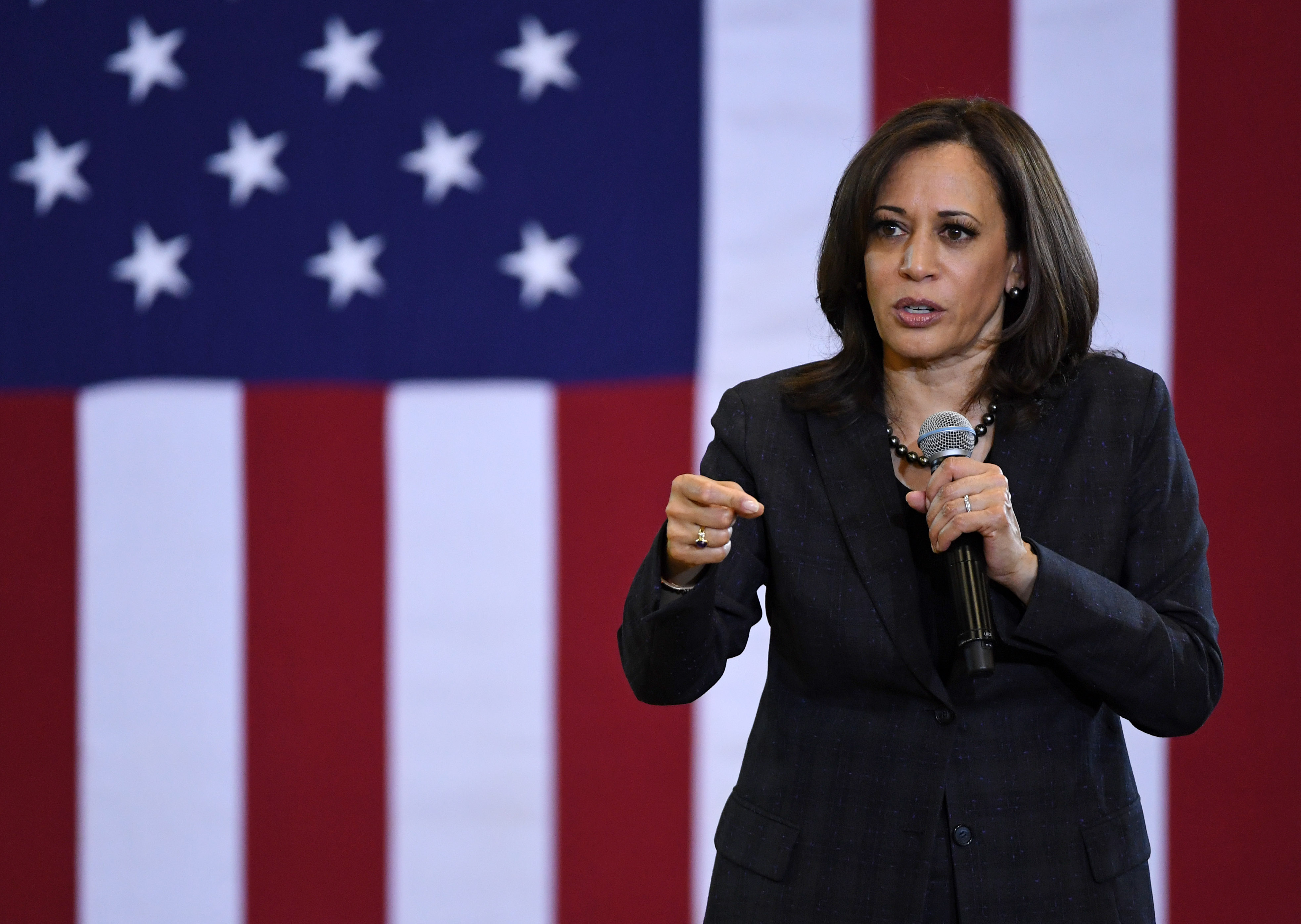 Harris, in a black suit, speaks in front of a giant American flag.
