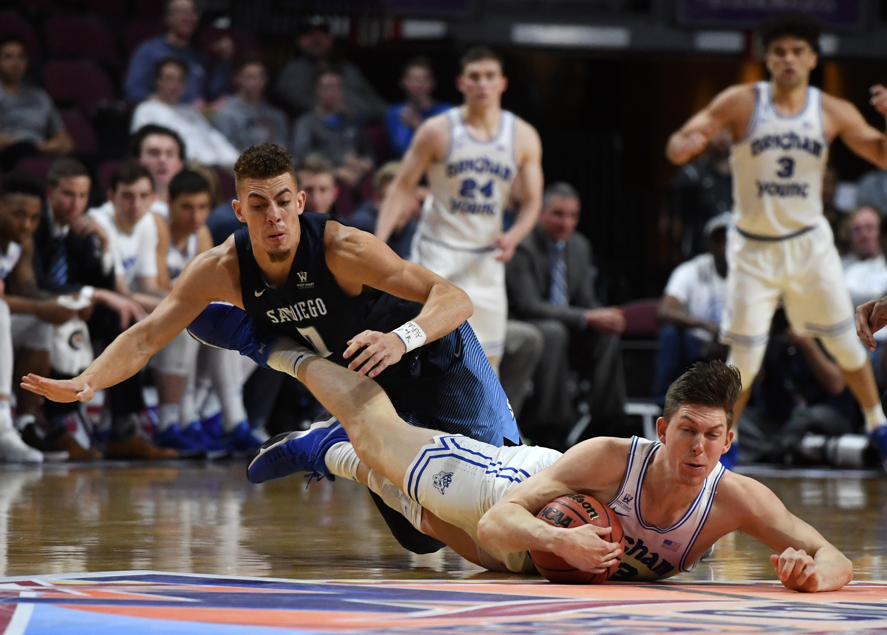 Isaiah Pineiro of the San Diego Toreros and Dalton Nixon of the Brigham Young Cougars go after a loose ball during a quarterfinal game of the West Coast Conference basketball tournament at the Orleans Arena on March 3, 2018 in Las Vegas, Nevada. The Cougars won 85-79.