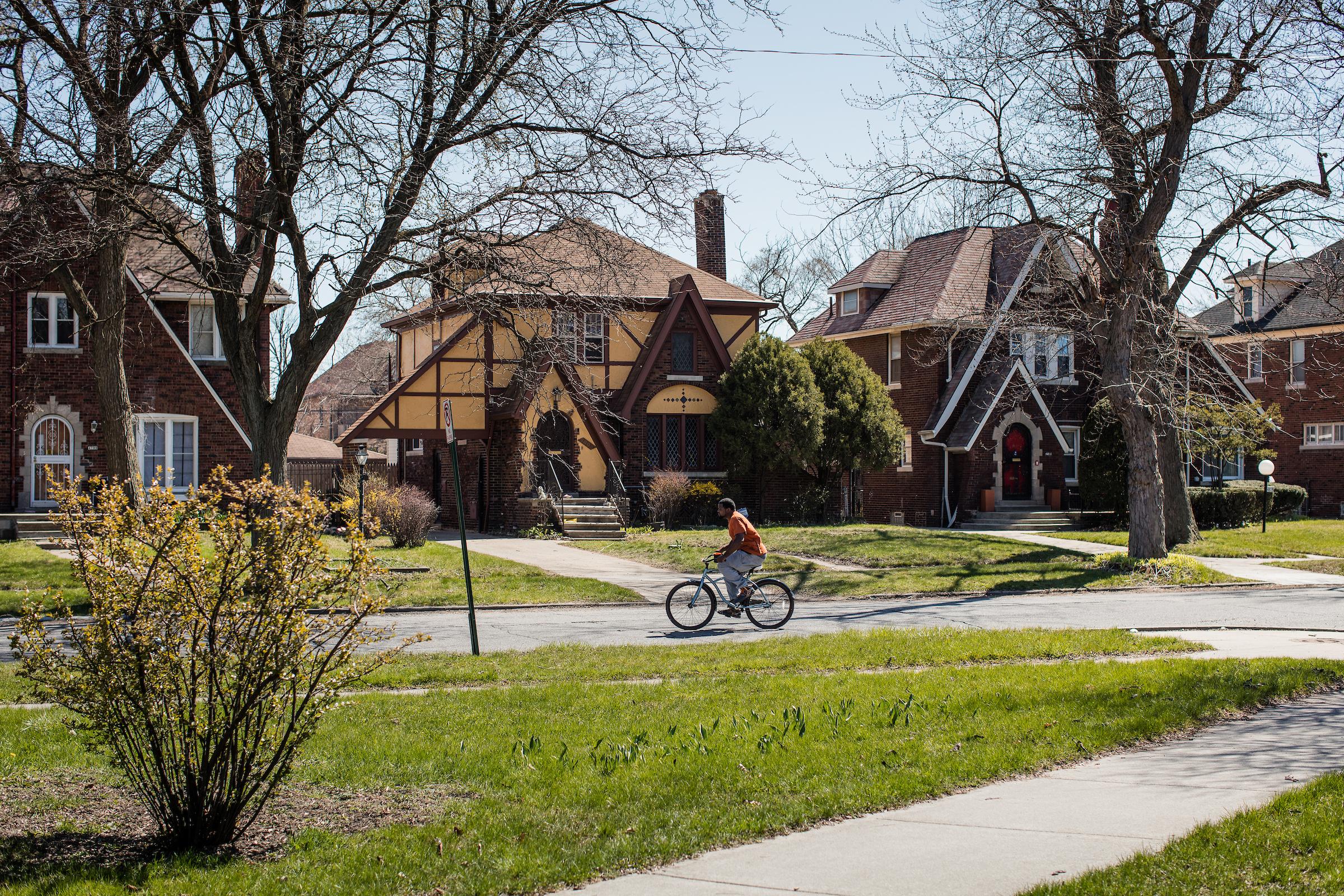 A neighborhood street, with three tudor style houses, a man on a bike is riding by.