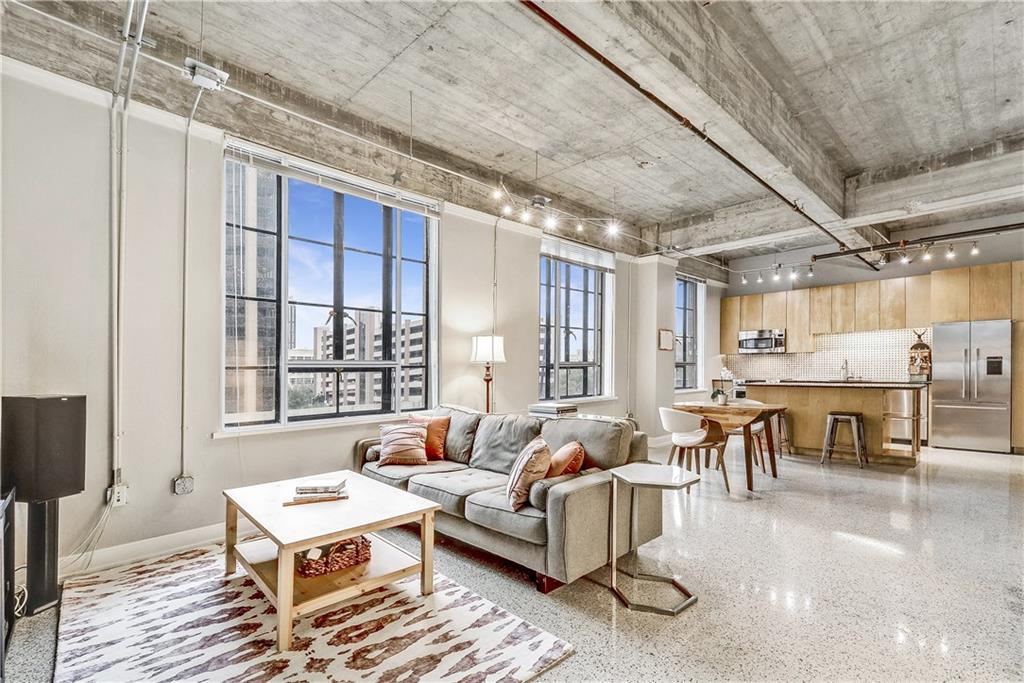 A photo of an open loft apartment with terrazzo floors, a very high concrete ceiling with exposed duct work, and two large multipaned windows with tops of tall buildings outside. A couch and a square coffee table are arranged on rug in the living area, and the kitchen is on the back wall.