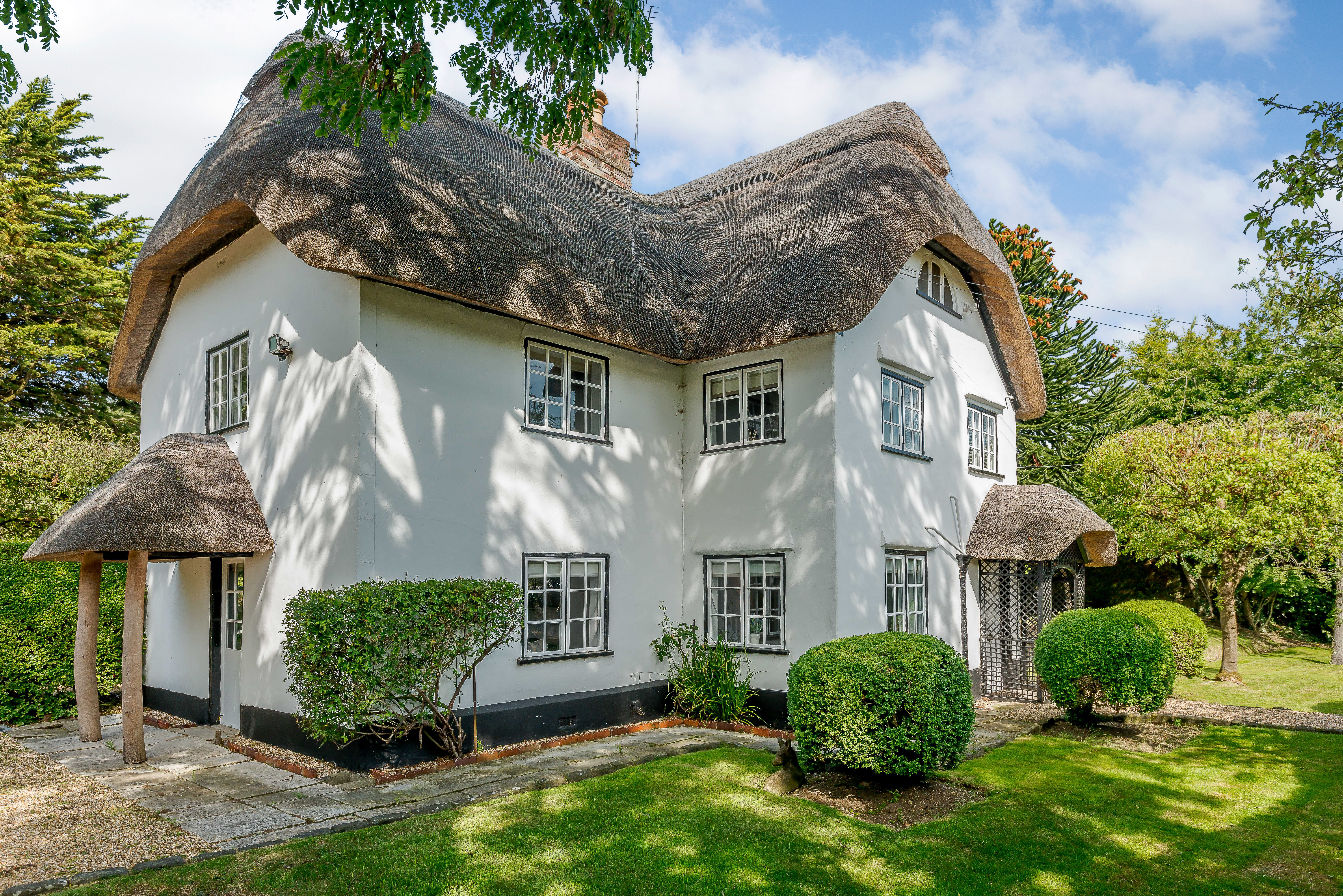 Large cottage with white plaster walls and thatched roof.