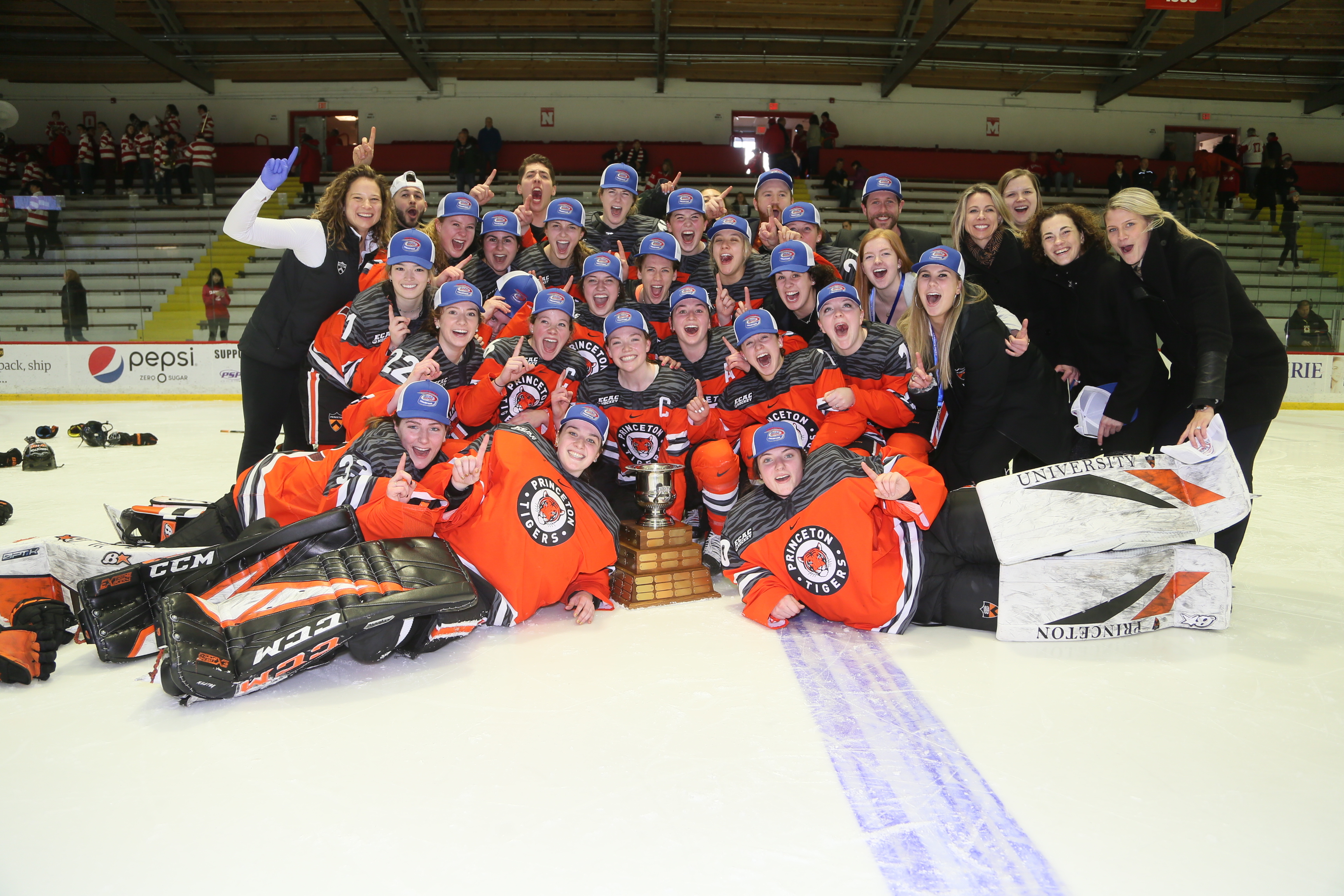 Princeton's players, coaches, and staff members pose on the ice with the ECAC Championship trophy following their 3-2 overtime victory over Cornell.