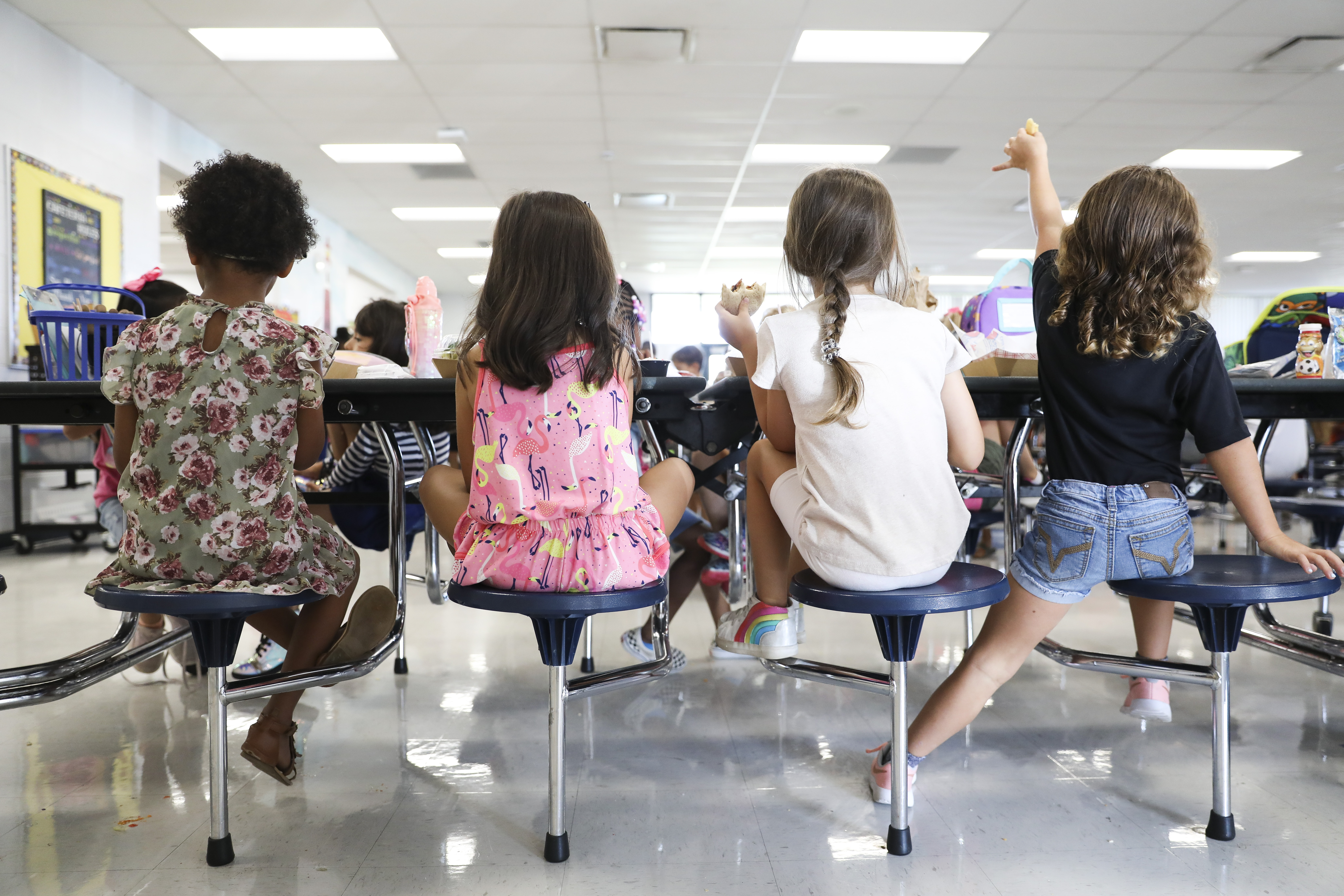 Four girls sitting at cafeteria table.