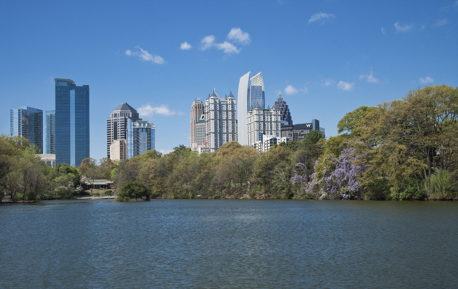 The Midtown skyline sits behind the lake at Piedmont Park.