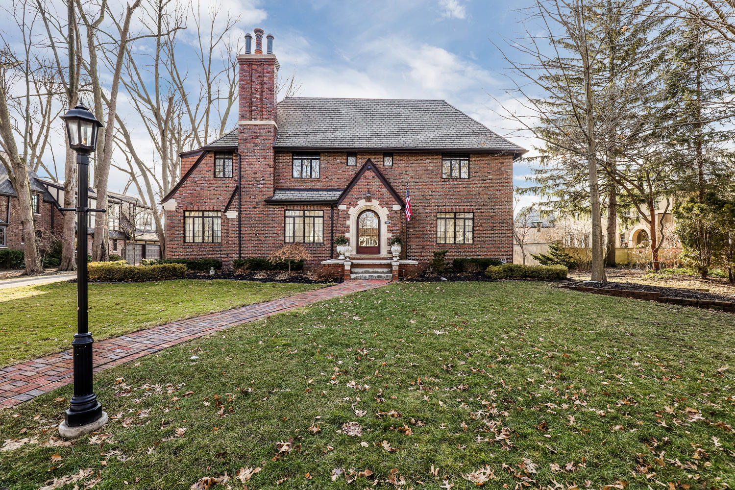 A two story brick house with an arched stone entryway and tall chimney. There's a large yard with leaves on the ground and a slightly curved brick walkway.