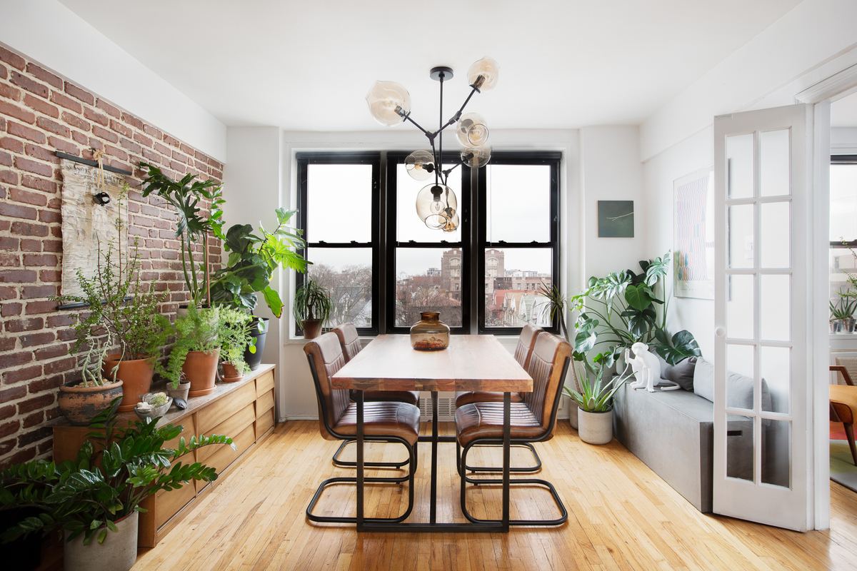 A dining area with hardwood floors, modern pendant lights, several planters, exposed brick, and French doors that lead to another room.