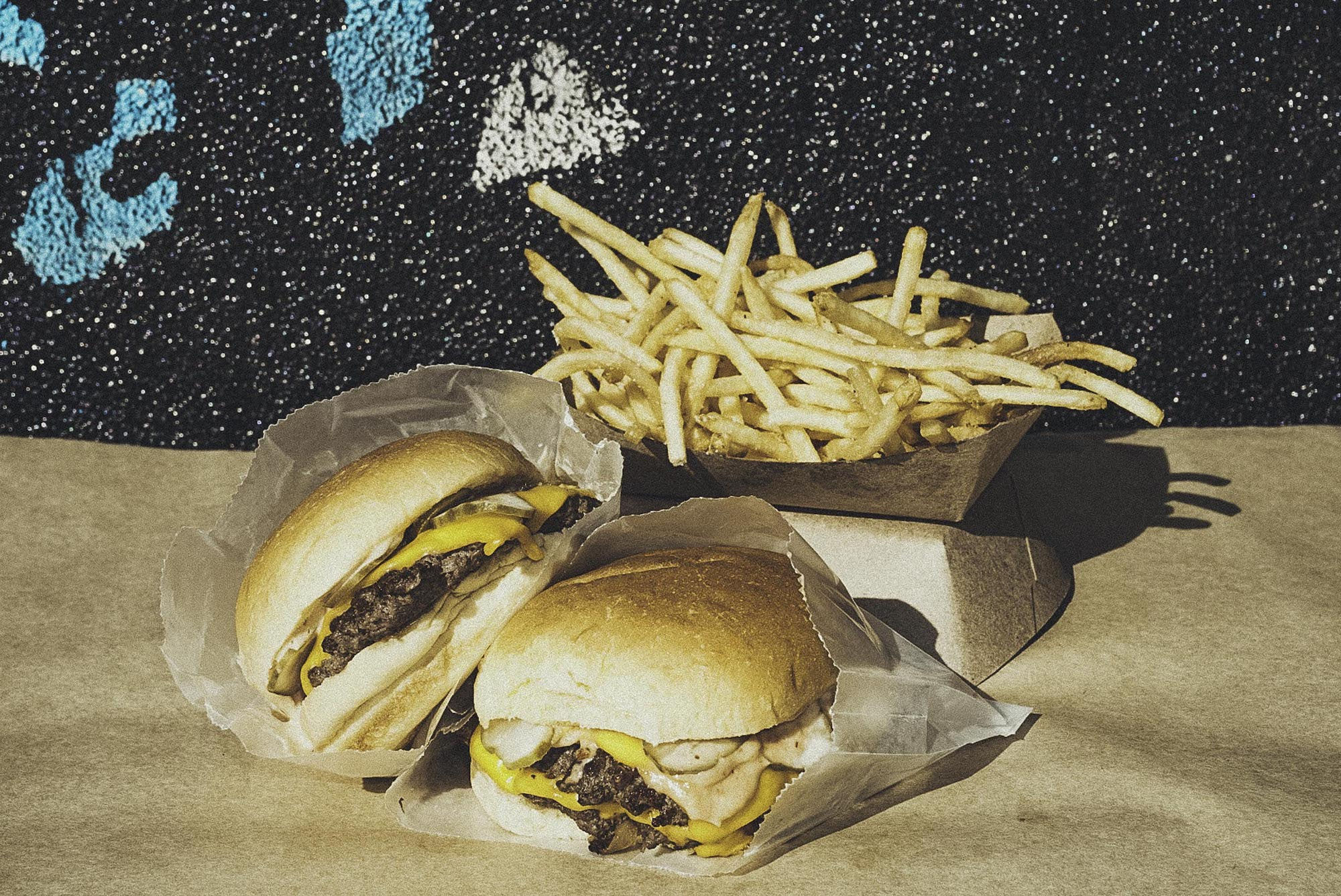 Two burgers perched atop one another with fries and a colorful background.