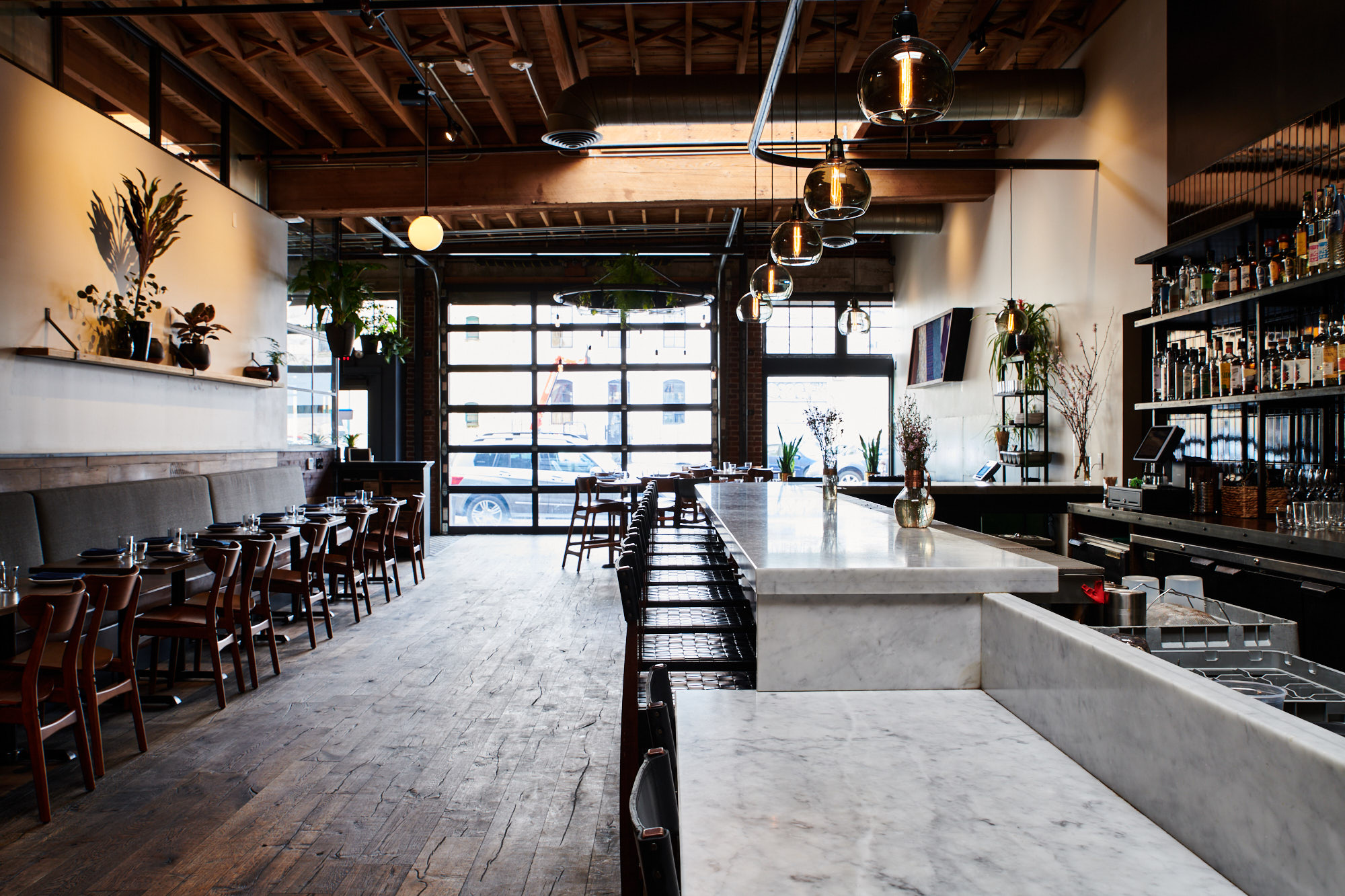 Looking at Bar King from the kitchen, a long white marble bar stretches toward a large garage window, bathed in light. To the left, a line of cushioned banquettes line the wall, with a line of plants on a shelf above.
