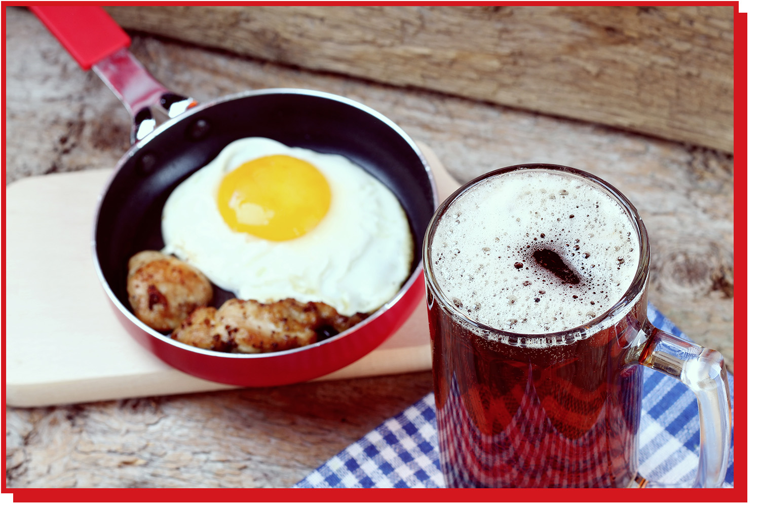 Pint of beer next to a small skillet containing fried egg and breakfast sausage.