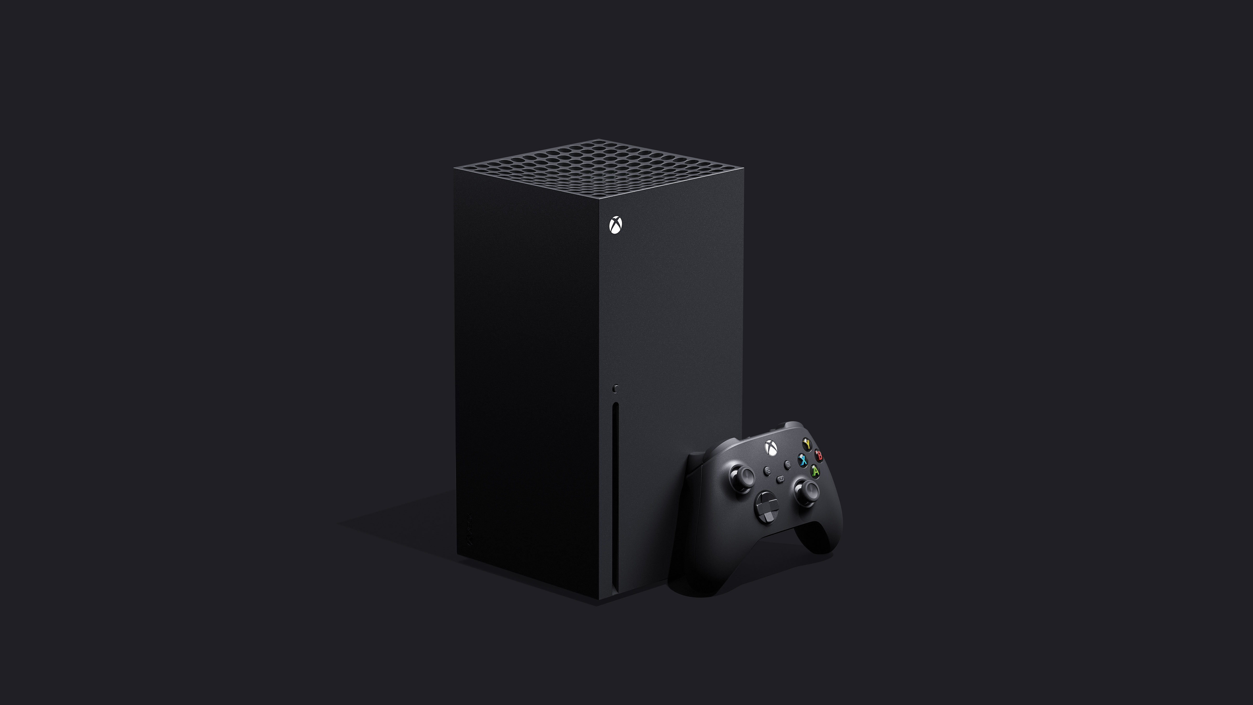 front left angle shot of Xbox Series X with controller standing in front of the console's bottom right corner