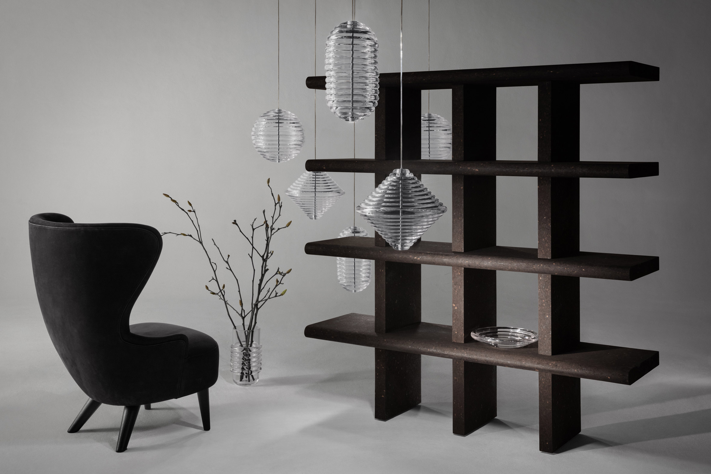 Chair sitting in front of cork shelving unit.