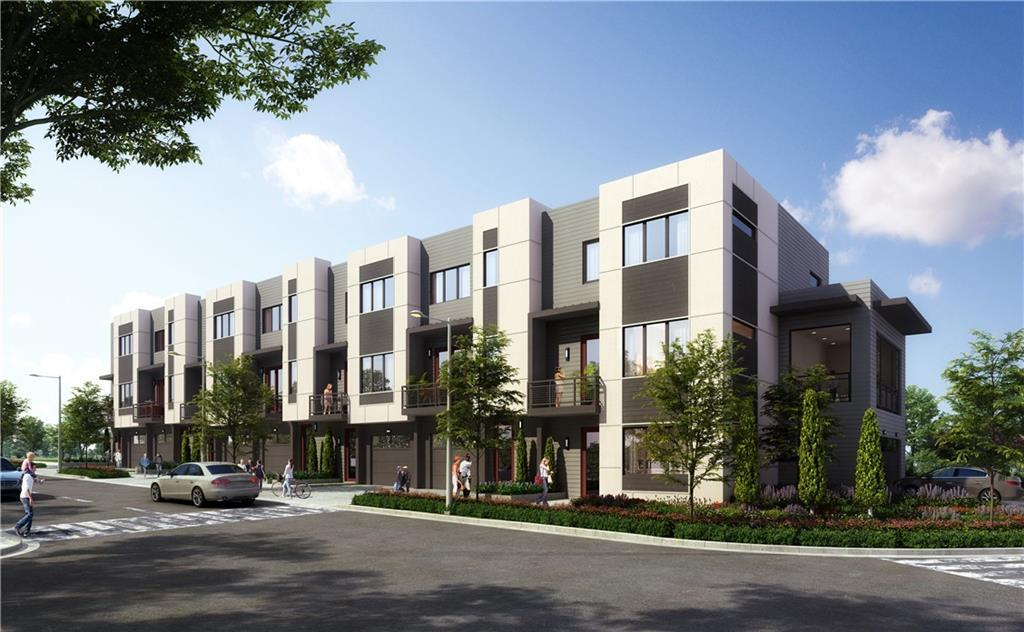 A row of white and gray townhomes with green trees in front and a silver car driving by.