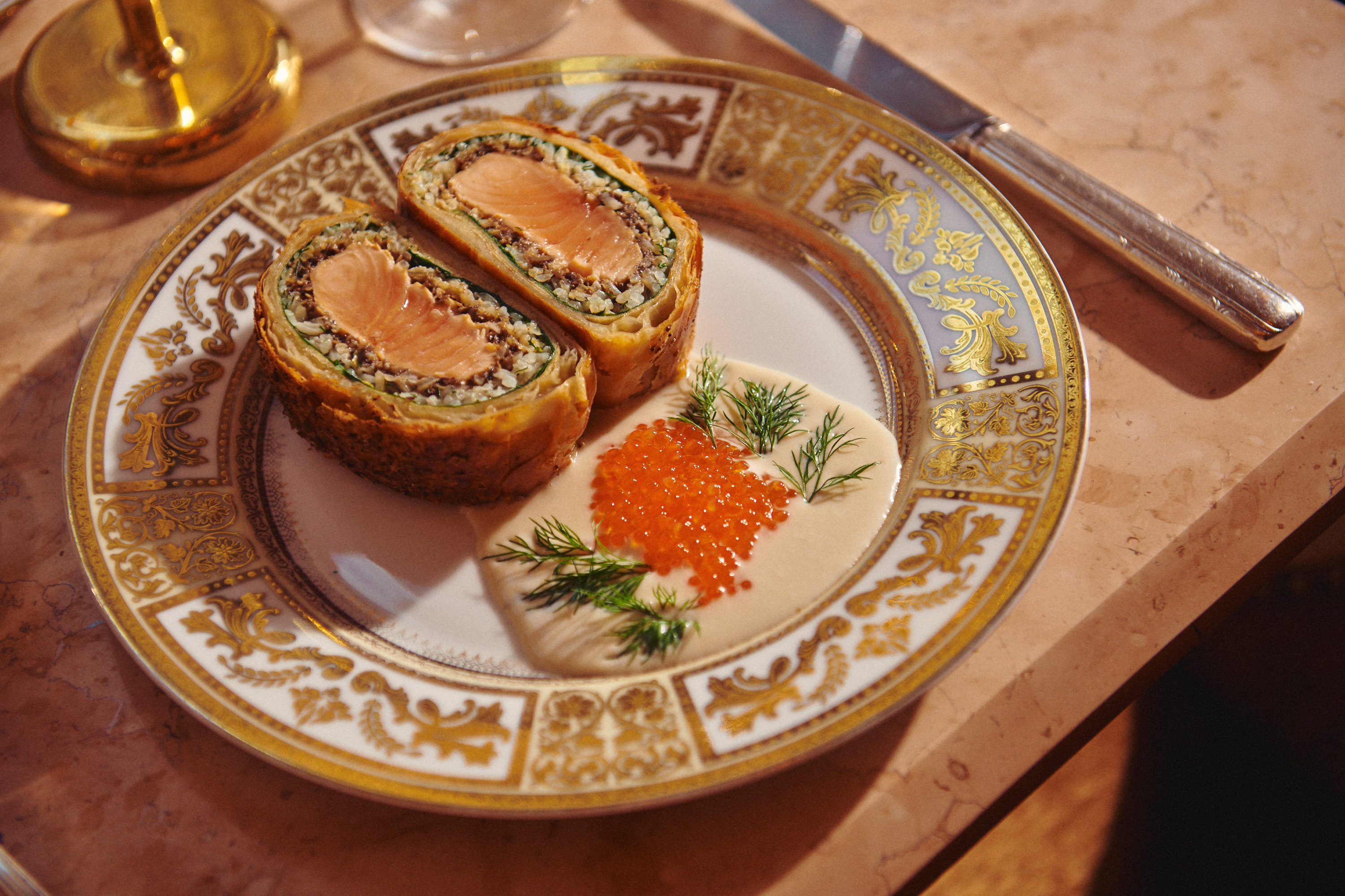 An ornate, gold-lined plate holds a Russian fish pie, with a creamy sauce next to it.