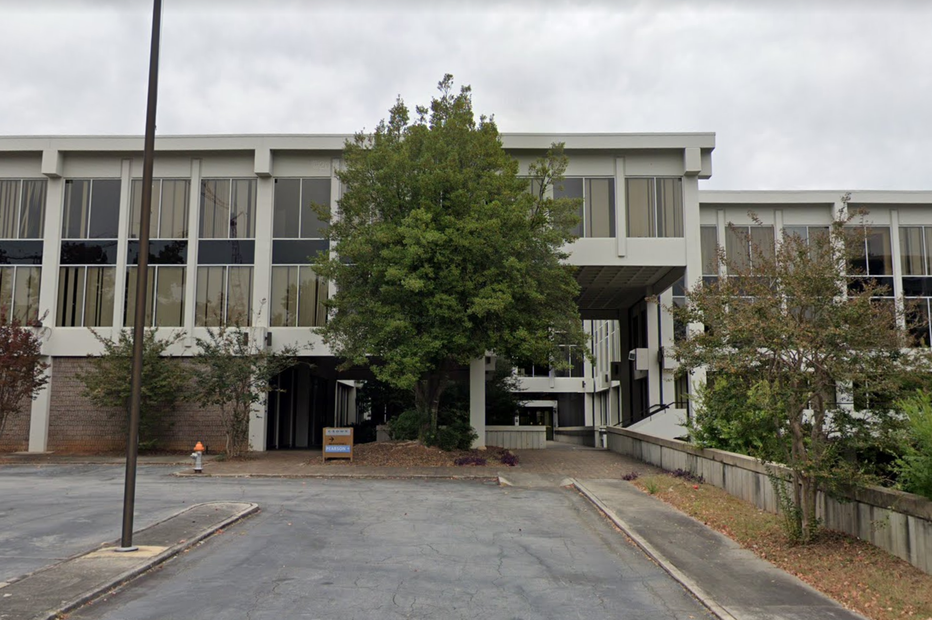 A plain three-story office building with a tree out front.