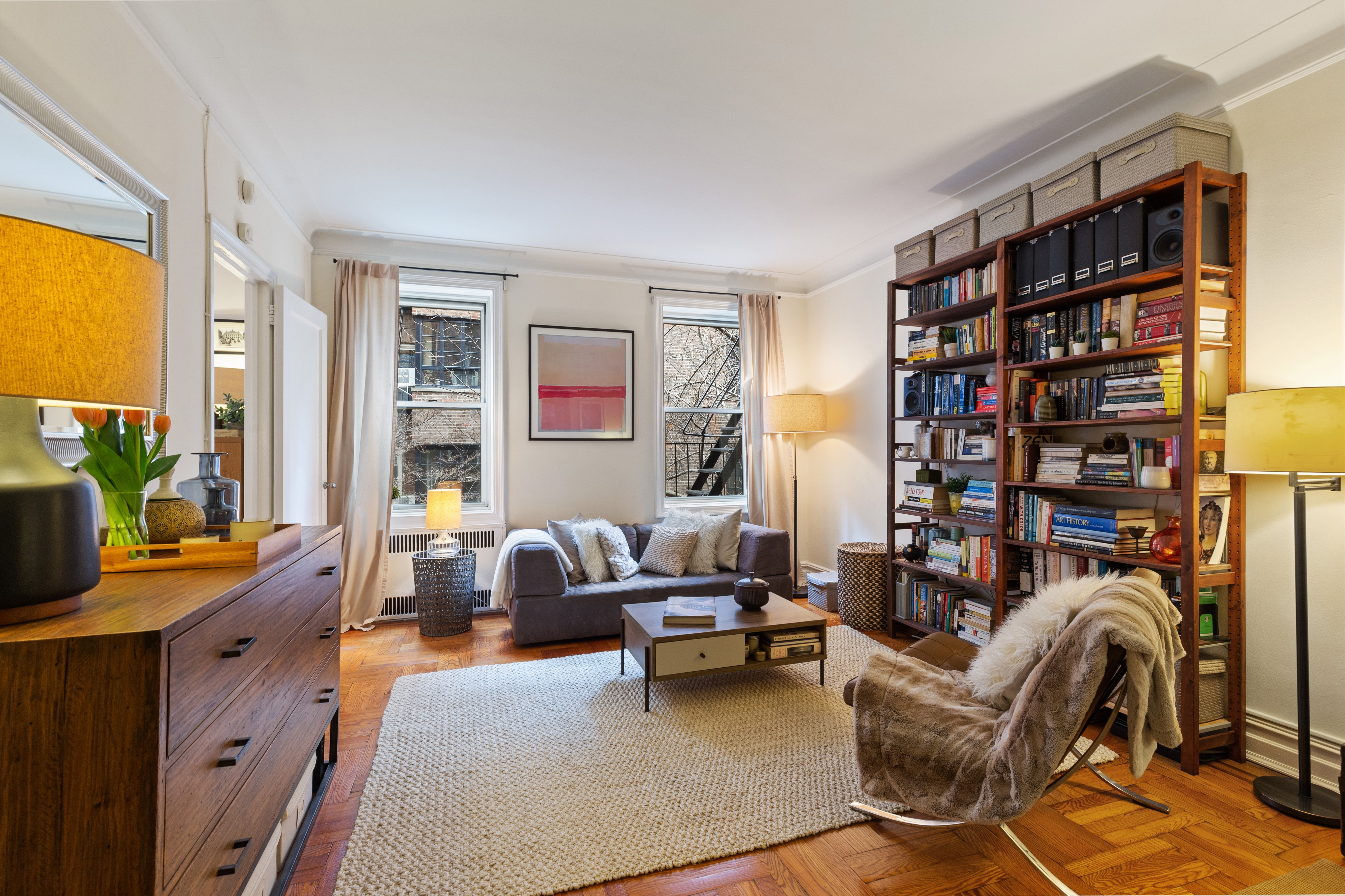 A living room with hardwood floors, a large wooden bookshelf, two windows, a beige rug, and a small couch.