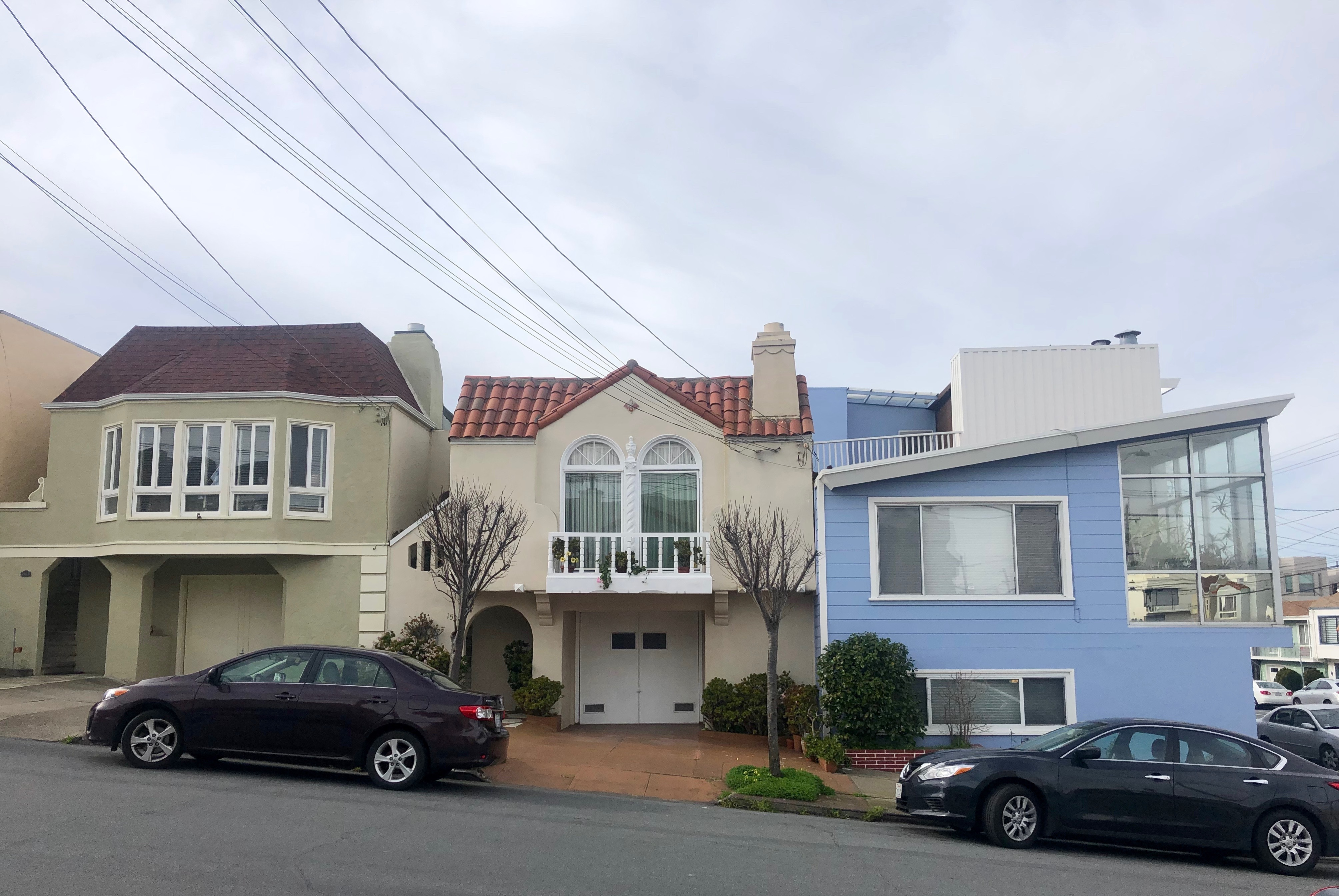 Three colorful single-family houses lining a street in San Francisco.