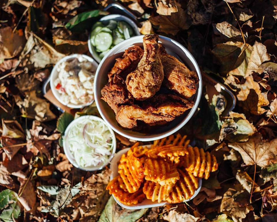 A bucket of fried chicken from Bucktown Chicken & Fish sits on the ground, which is covered with fallen leaves. There are also waffle fries and other sides.