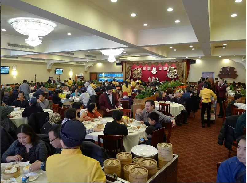 A grand banquet-style dining room with chandeliers and tons of diners as dim sum carts roll by