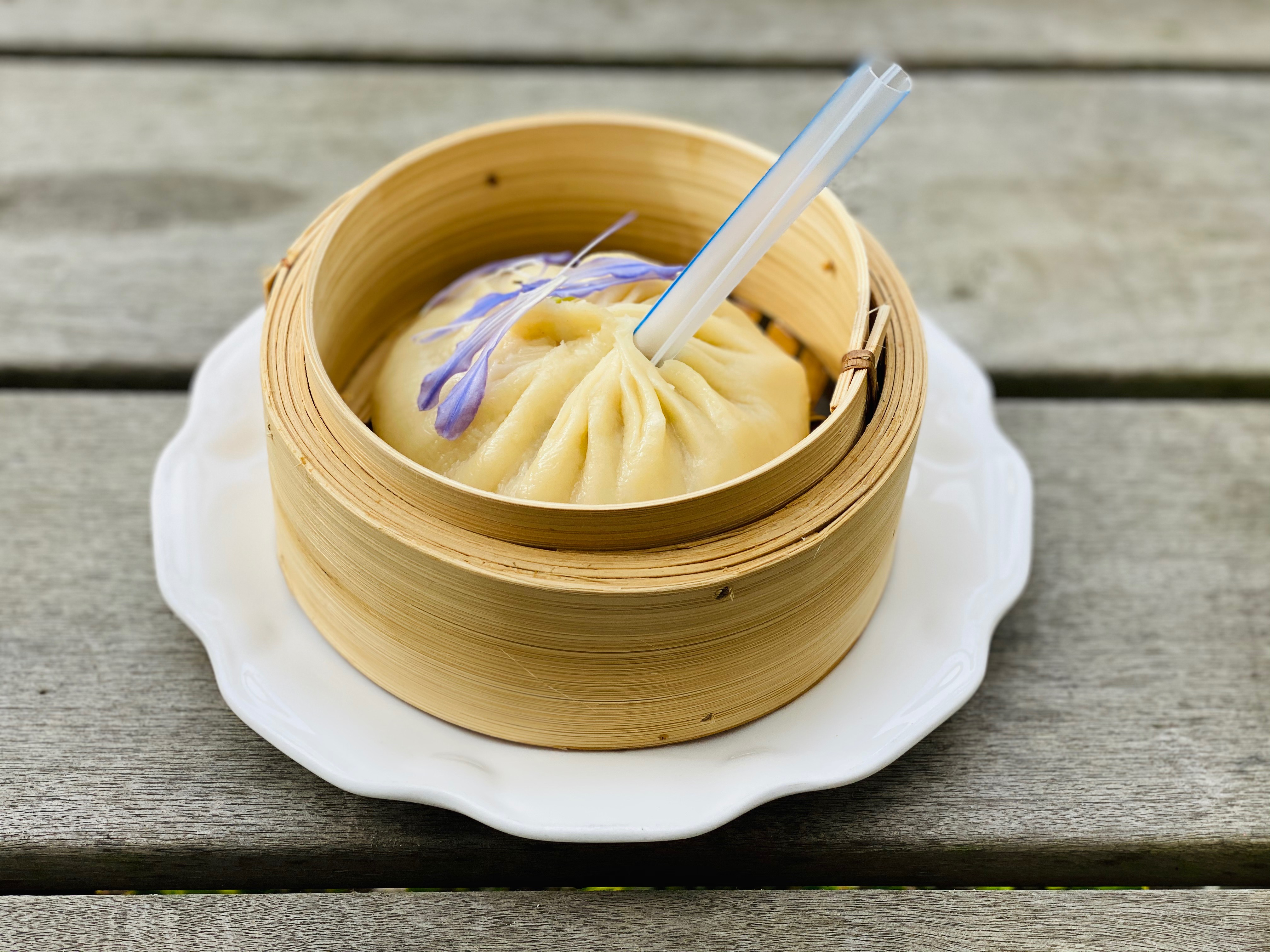 A jumbo-size soup dumpling, served with a straw