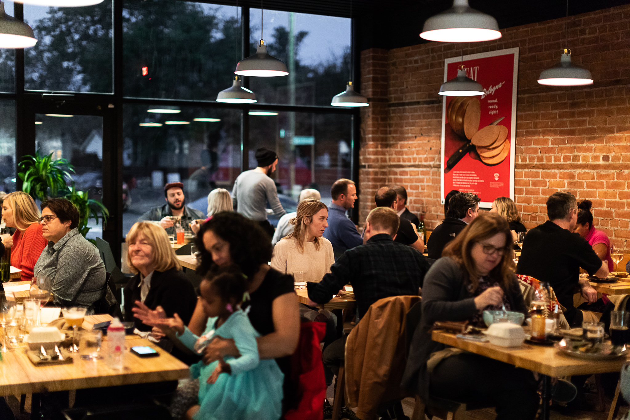 Customers fill the well-lit dining room at Marrow. The photo faces out towards the window and brick walls.