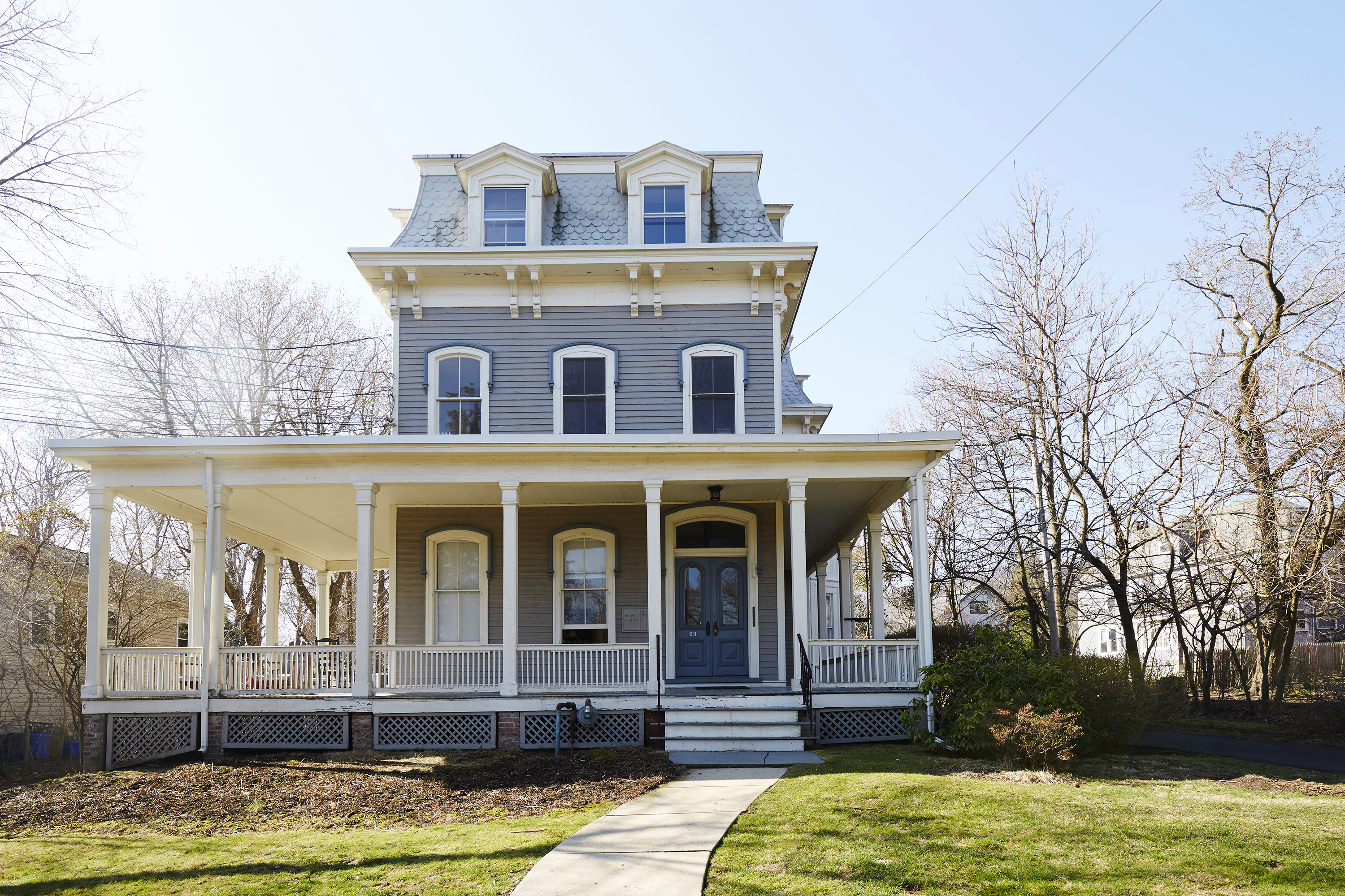 A three story, Victorian style home. The ground floor has a wrap around large porch, the home is painted a light grey with a blue door and white trim.