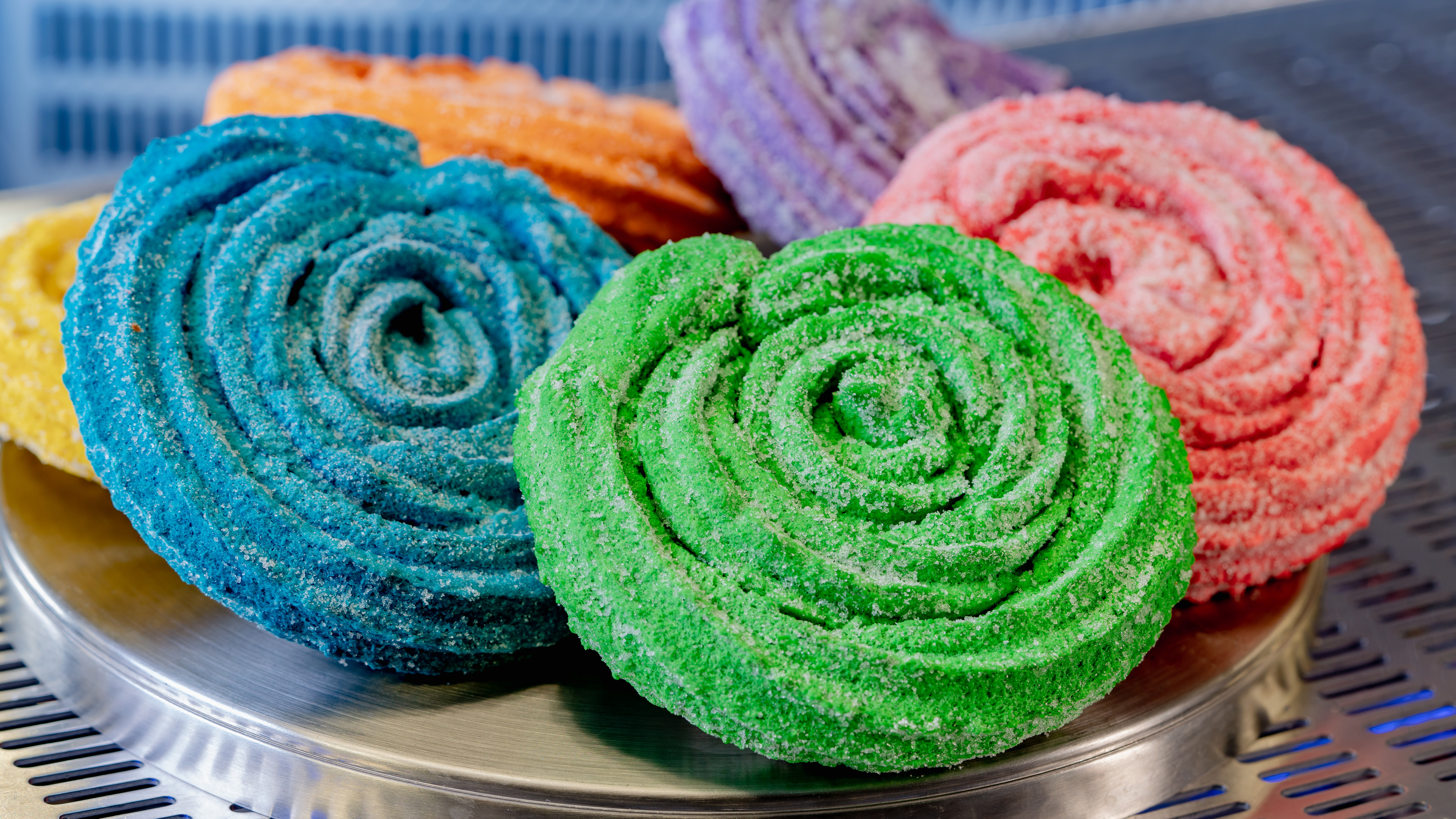 Bright round churros in various colors of the rainbow on a metal tray