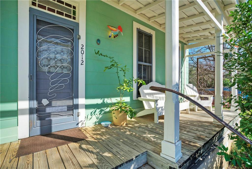Photo of a covered porch attached to a vintage home. The front door has a blocked glass transom. There's a bench under a large window and three posts along the front.
