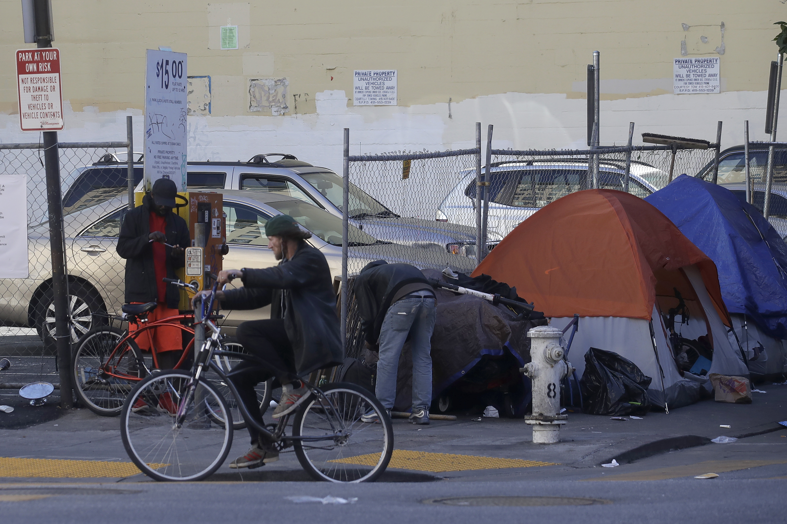 A man rides a bicycle in front of tents on a sidewalk in San Francisco.