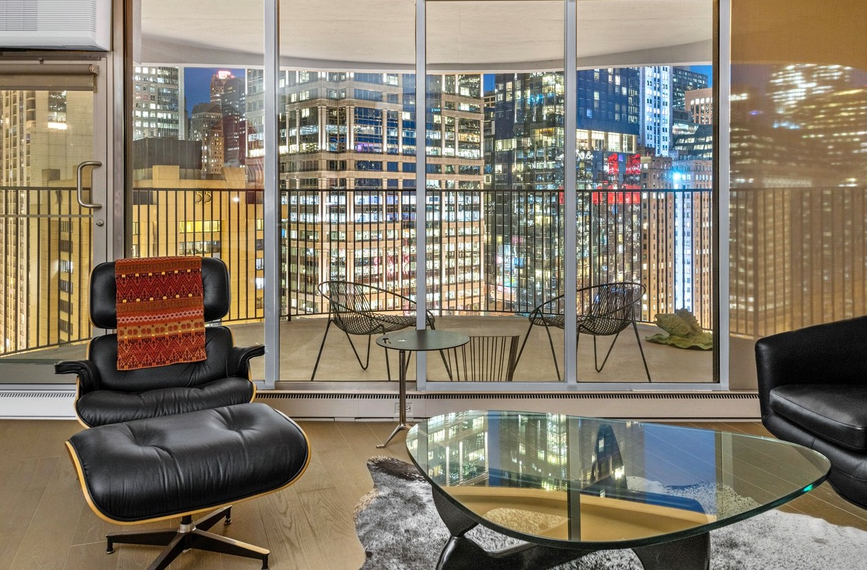 An Eames chair and Noguchi coffee table in a living room with floor to ceiling glass overlooking a balcony and a row of tall skyscrapers at night.