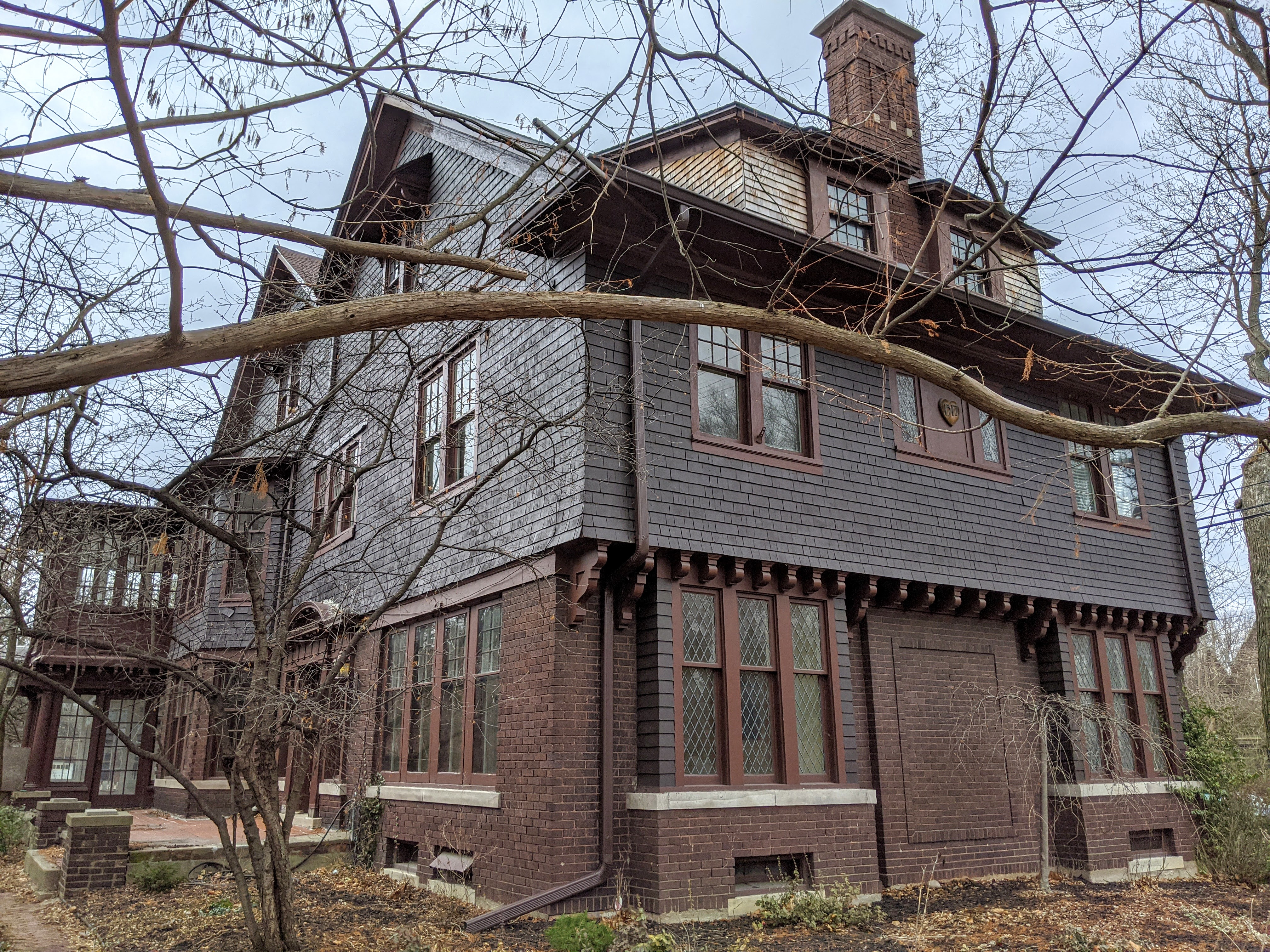 A long home with brick first floor and cedar shake siding over the second story.