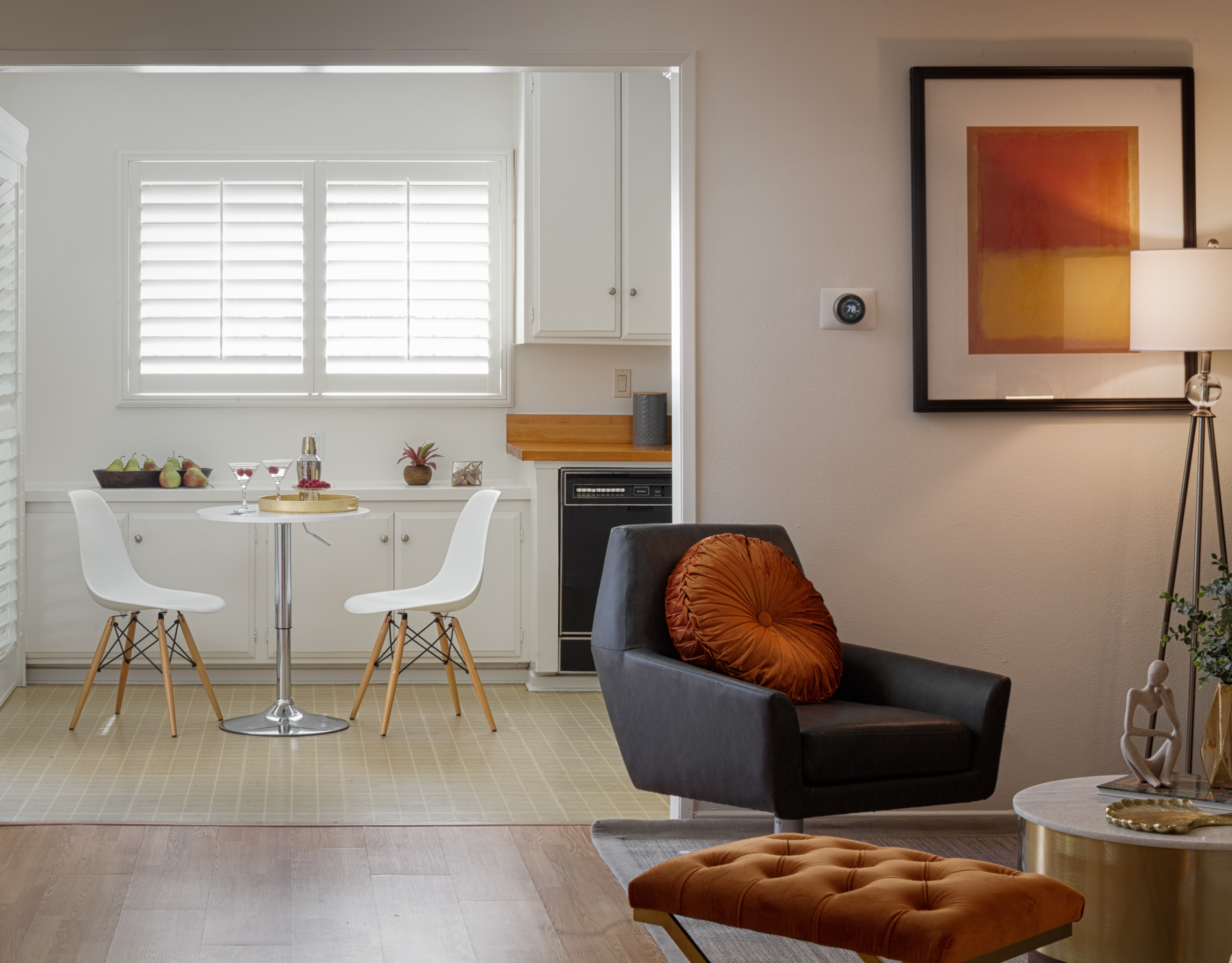 A view from one room into another, with a chair visible in the first room and a small table and chairs in the far room