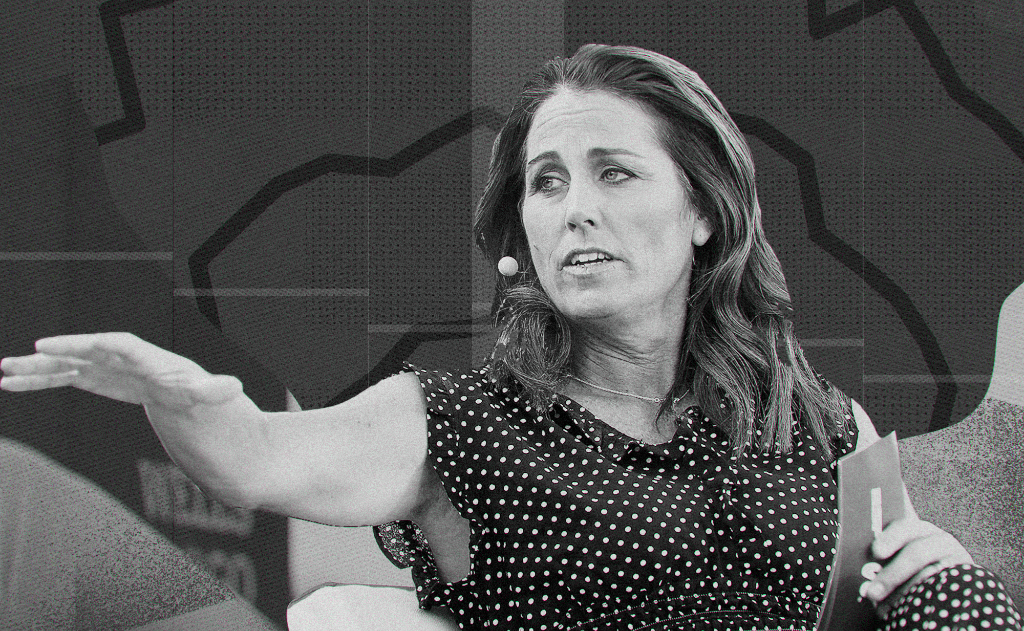 Black and white photo of Julie Foudy at a panel, gesturing to the person next to her.
