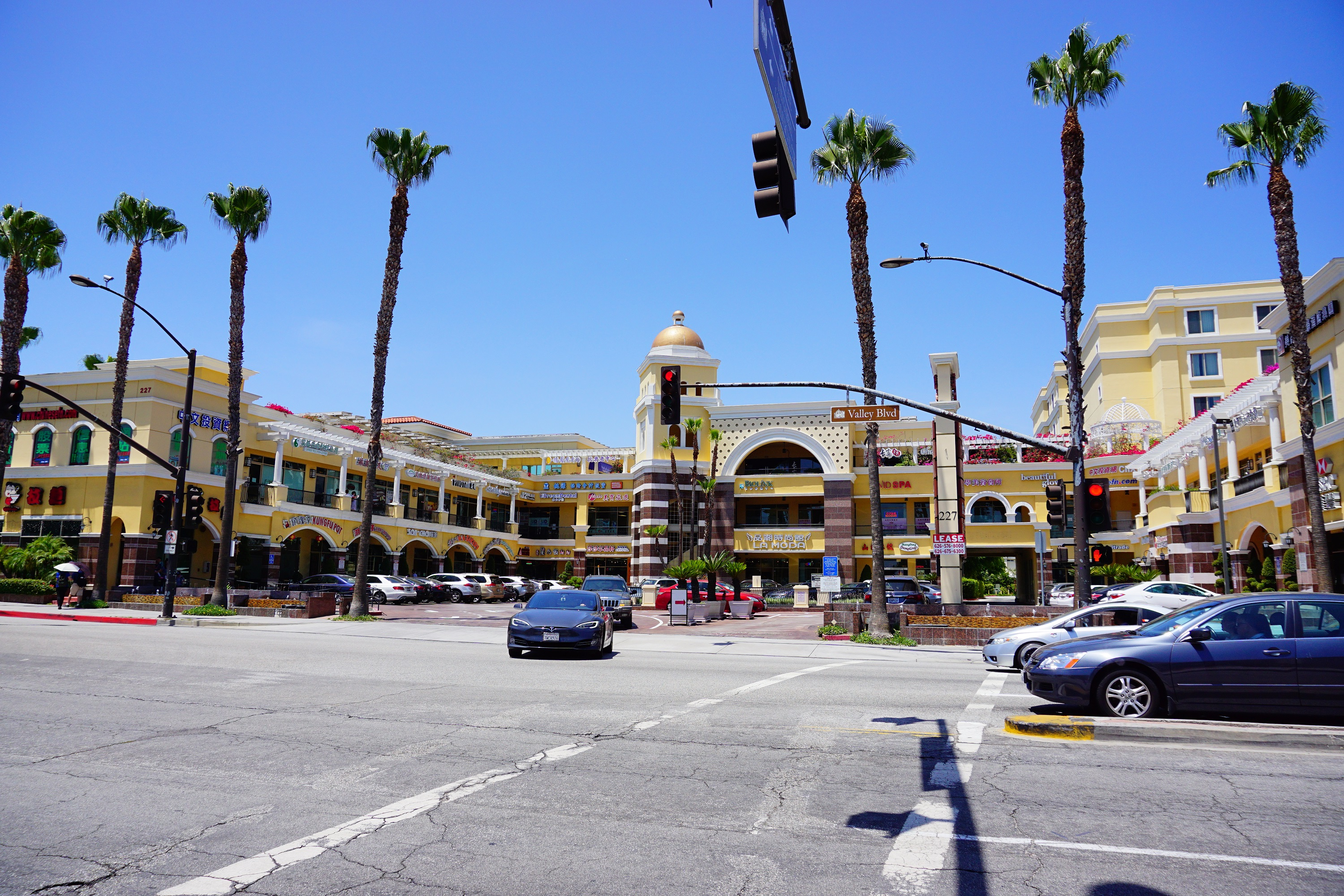 Strip mall with restaurants in San Gabriel, California with palm trees.
