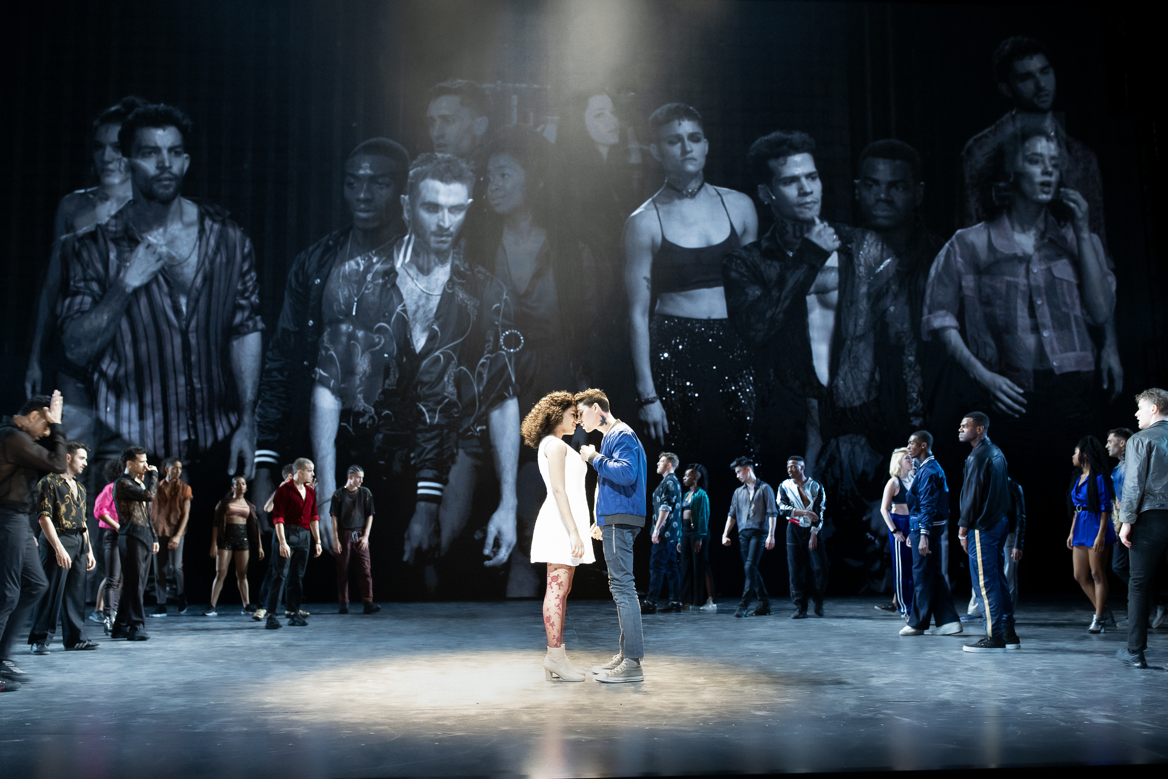 A man and woman embrace at the center of a stage, under a spotlight. Behind them, a crowd lurks in a circle, and above the crowd are larger-than-life video projections of the cast.