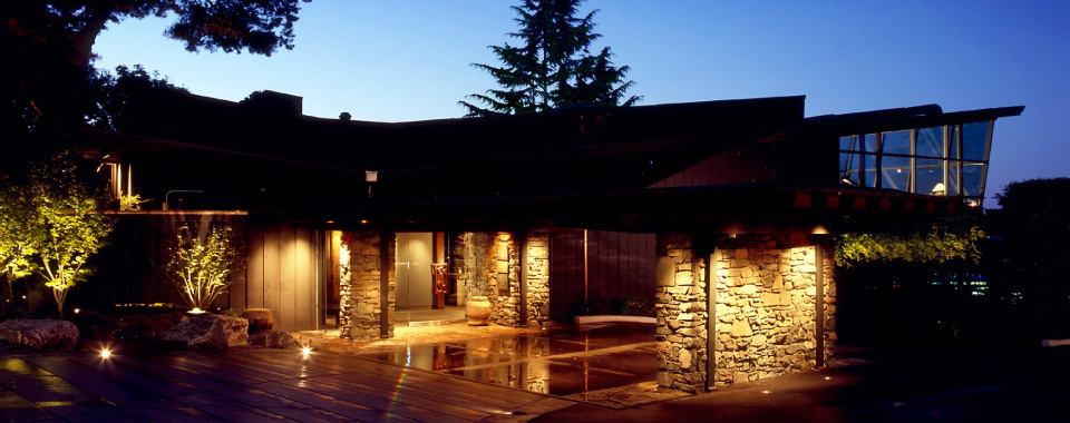 An exterior view of Canlis restaurant at night, with stone walls lighted in the foreground and the tops of trees seen in the background.